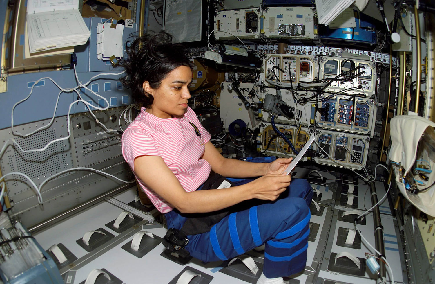 NASA astronaut Kalpana Chawla looks over a procedures checklist in the SPACEHAB Research Double Module aboard the Space Shuttle Columbia, on Jan. 27, 2003. Chawla was the first Indian-American astronaut and the first Indian woman to go to space. In 2003, Chawla was one of the seven crew members who perished in the Columbia disaster.