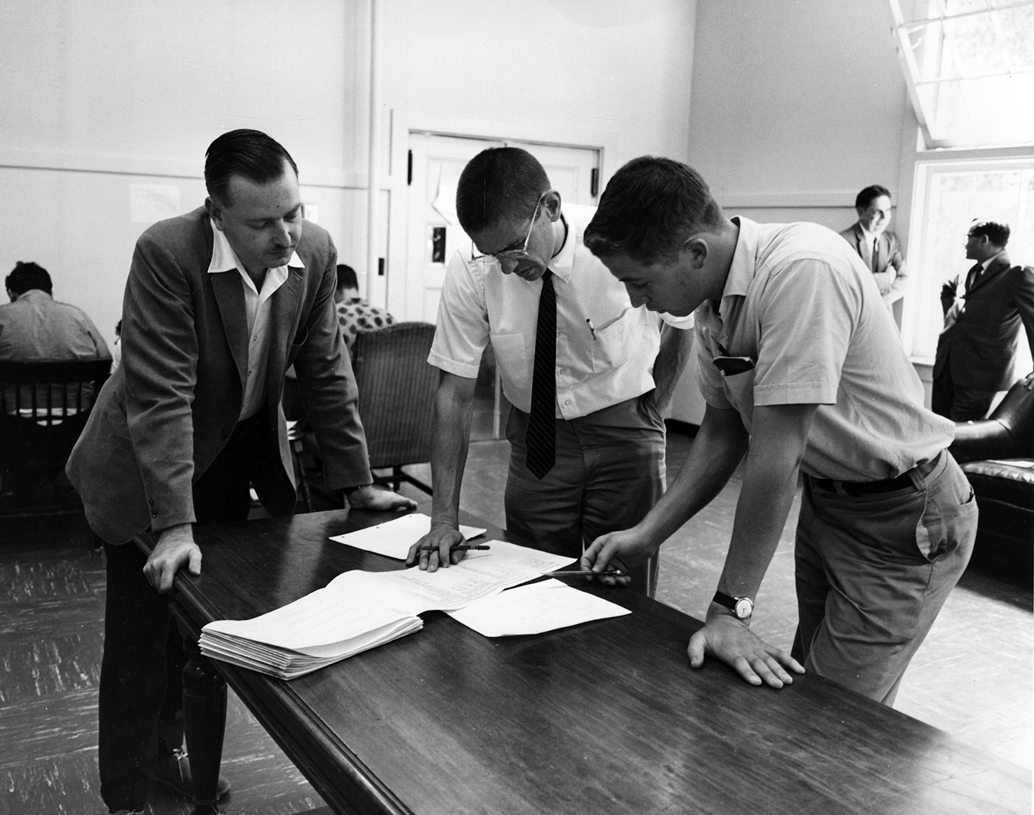 Early in BASIC's history, its creators, John Kemeny (left) and Thomas Kurtz (center) go over a program with a Dartmouth student