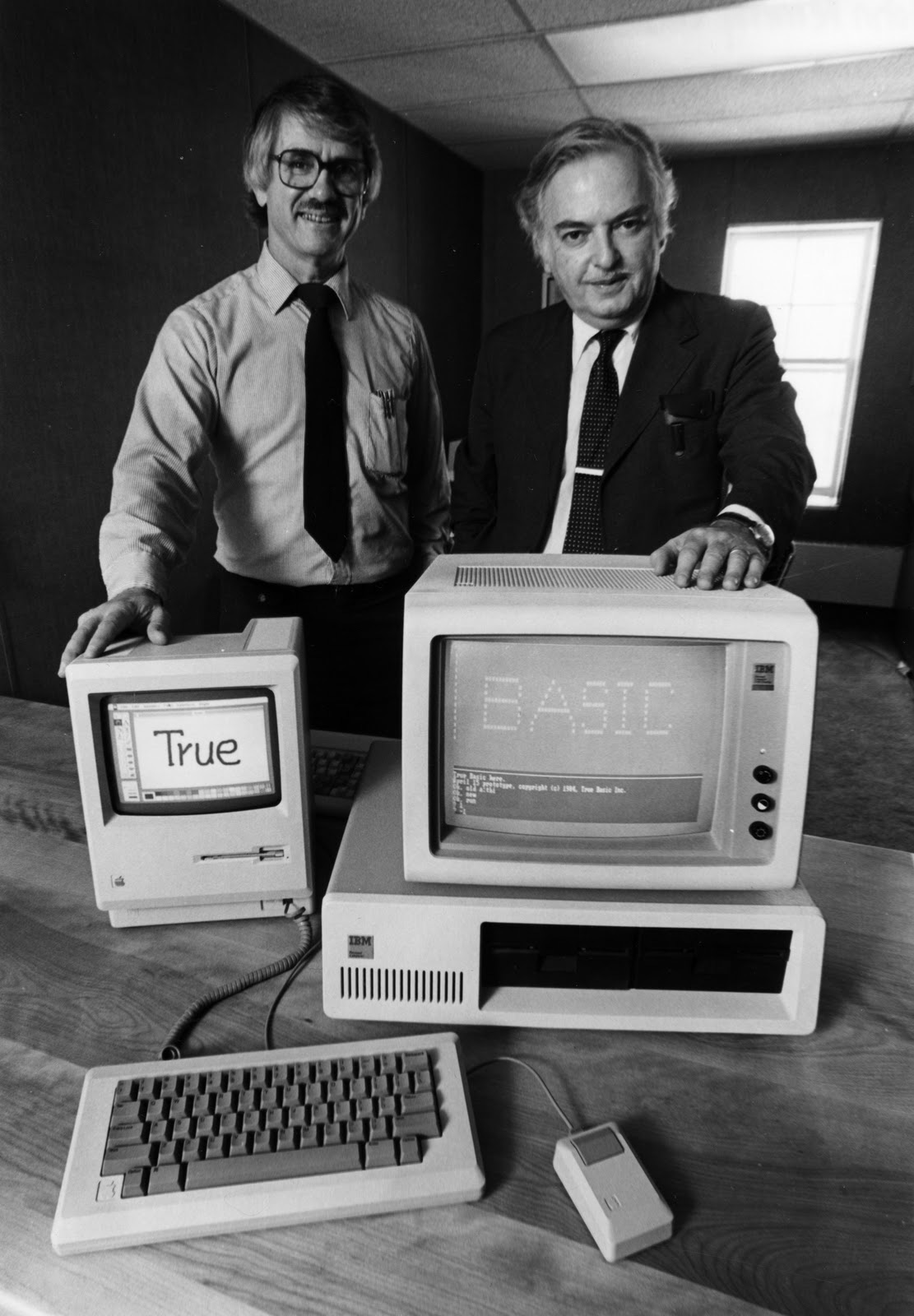 BASIC creators Thomas Kurtz (left) and John Kemeny in the mid-1980s, showing their True BASIC running on a Mac and an IBM PC
