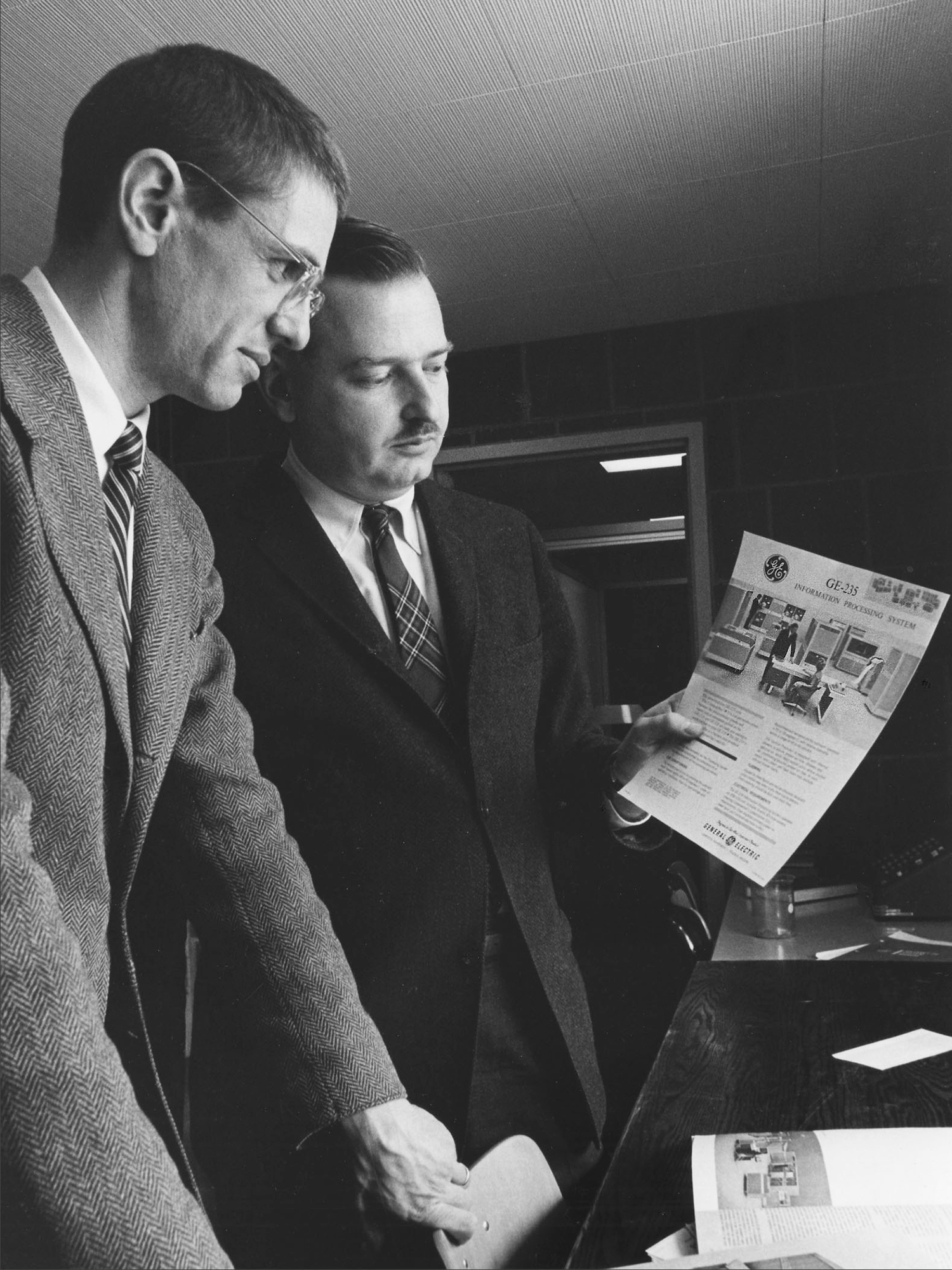 Tom Kurtz and John Kemeny examine a brochure for the GE-225 mainframe computer that powered the initial version of Dartmouth's time-sharing system