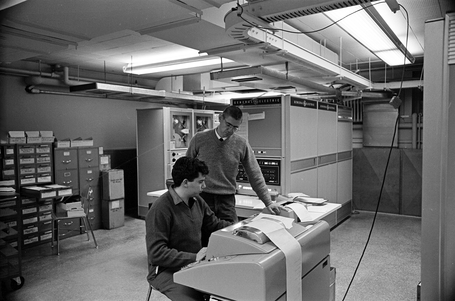Tom Kurtz (standing) works with Michael Busch, co-programmer of the DTSS, with the GE-225 mainframe in the background