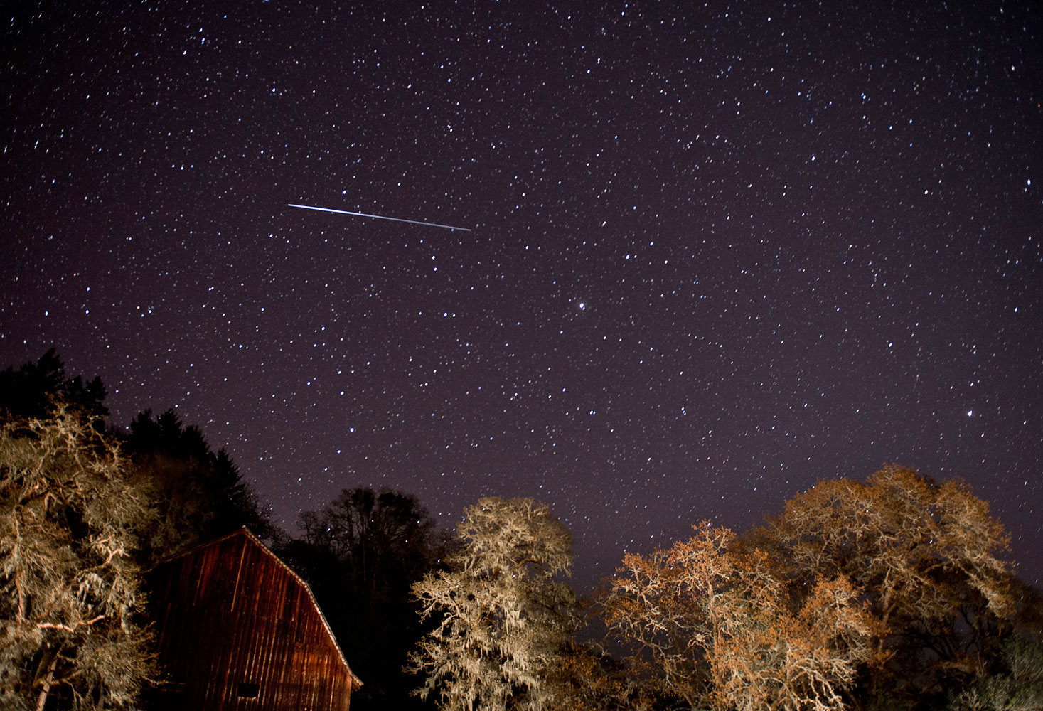 A meteor from the Lyrid meteor shower streaks through the sky above a barn along a country road near Oakland, Ore. April 21, 2012.