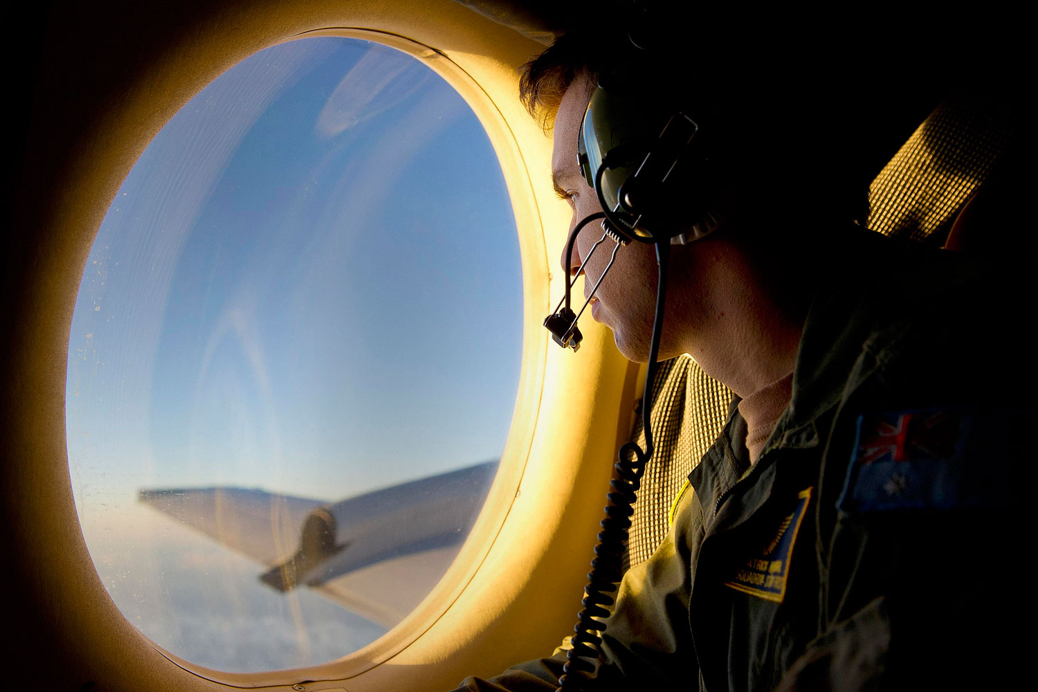 Royal Australian Air Force Airborne Electronics Analyst Sergeant Patrick Manser looks out of an observation window aboard a RAAF AP-3C Orion aircraft during the search in the southern Indian Ocean for debris from the missing Malaysian Airlines flight MH370.