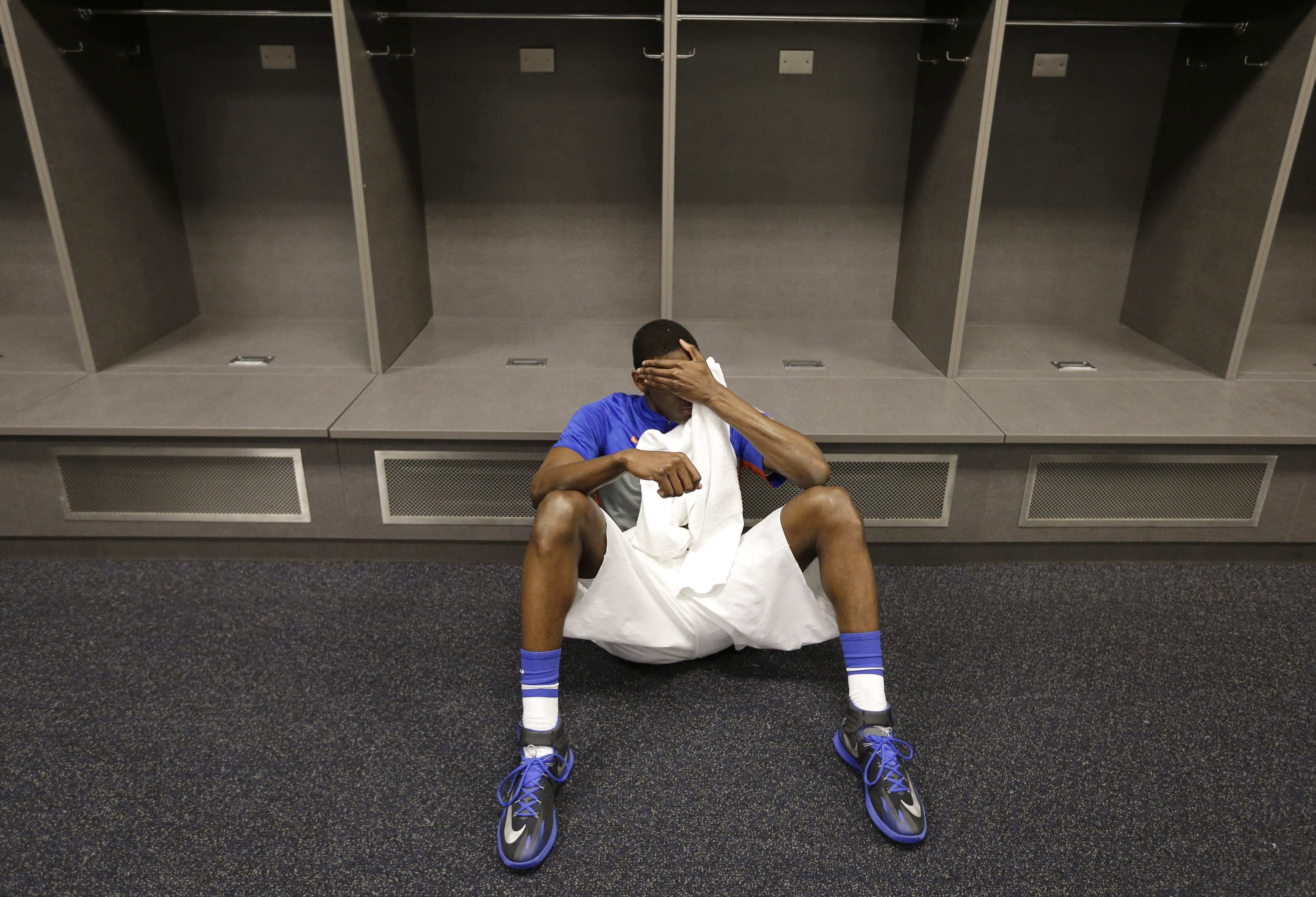 Florida forward Dorian Finney-Smith rests on the floor of the locker room after losing to Connecticut in the NCAA Tournament Final Four, April 5, 2014, in Arlington, Texas.  Connecticut won 63-53.