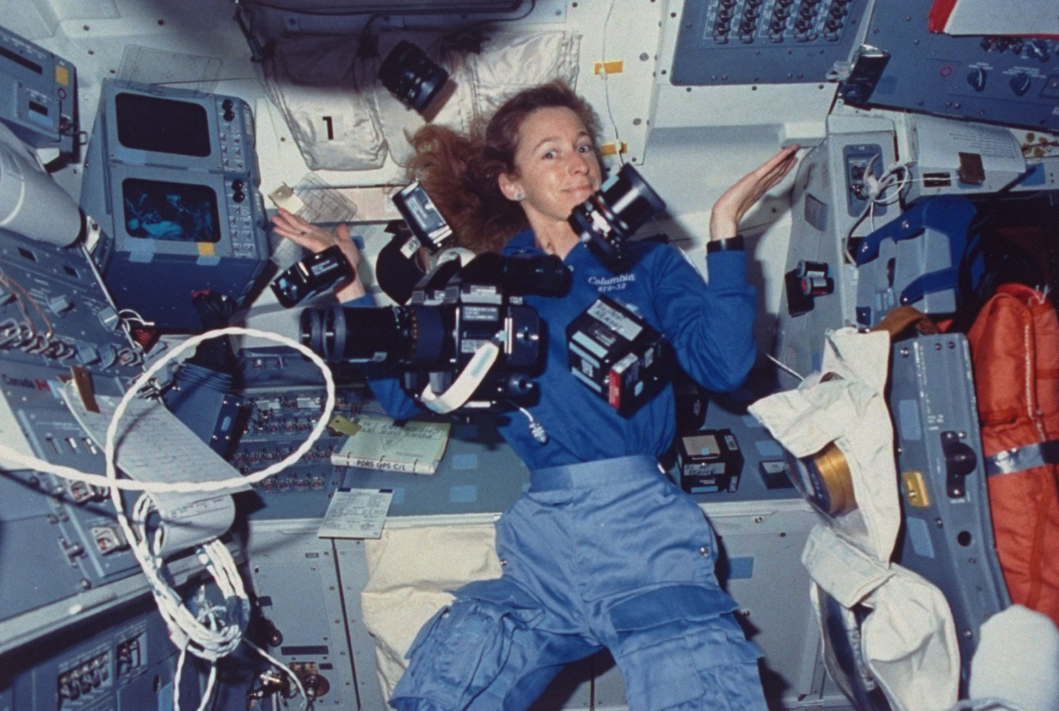 Astronaut Marsha Ivins, mission specialist aboard space shuttle Columbia, surrounded by cameras and supportive gear suspended by zero-gravity, on Jan. 1, 1990. Ivins flew in space five times.