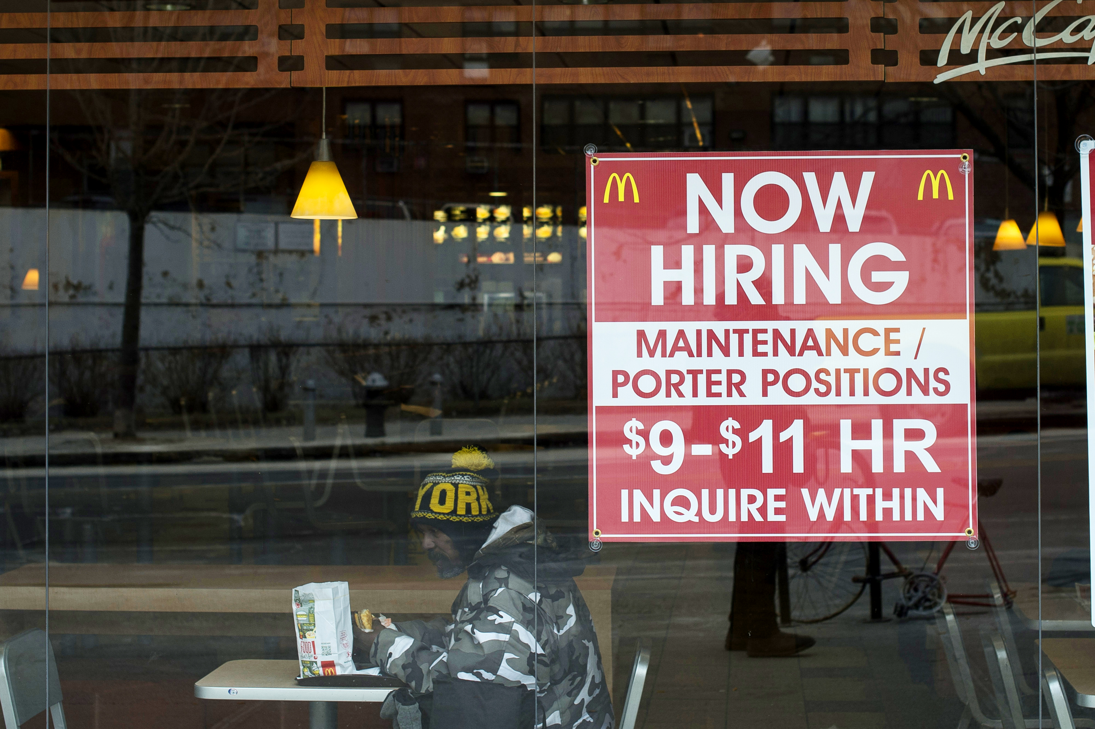 A diner sits next to a help wanted sign at a McDonalds restaurant in the Brooklyn borough of New York, on March 7, 2014.