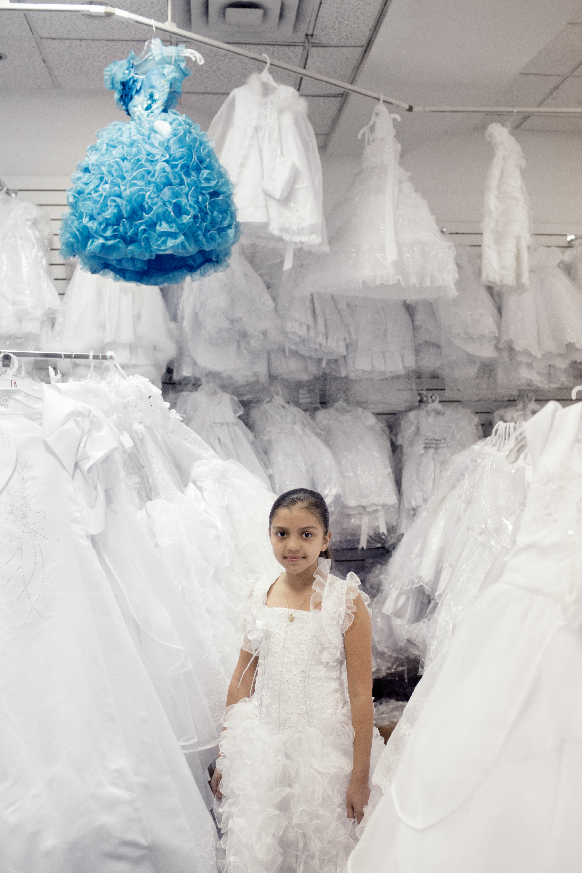 A portrait of Samantha Lujan, 10, trying on dresses for her First Communion at La Gran Plaza. Samantha's family are originally from Durango, Mexico. They moved to California and now live in Fort Worth.