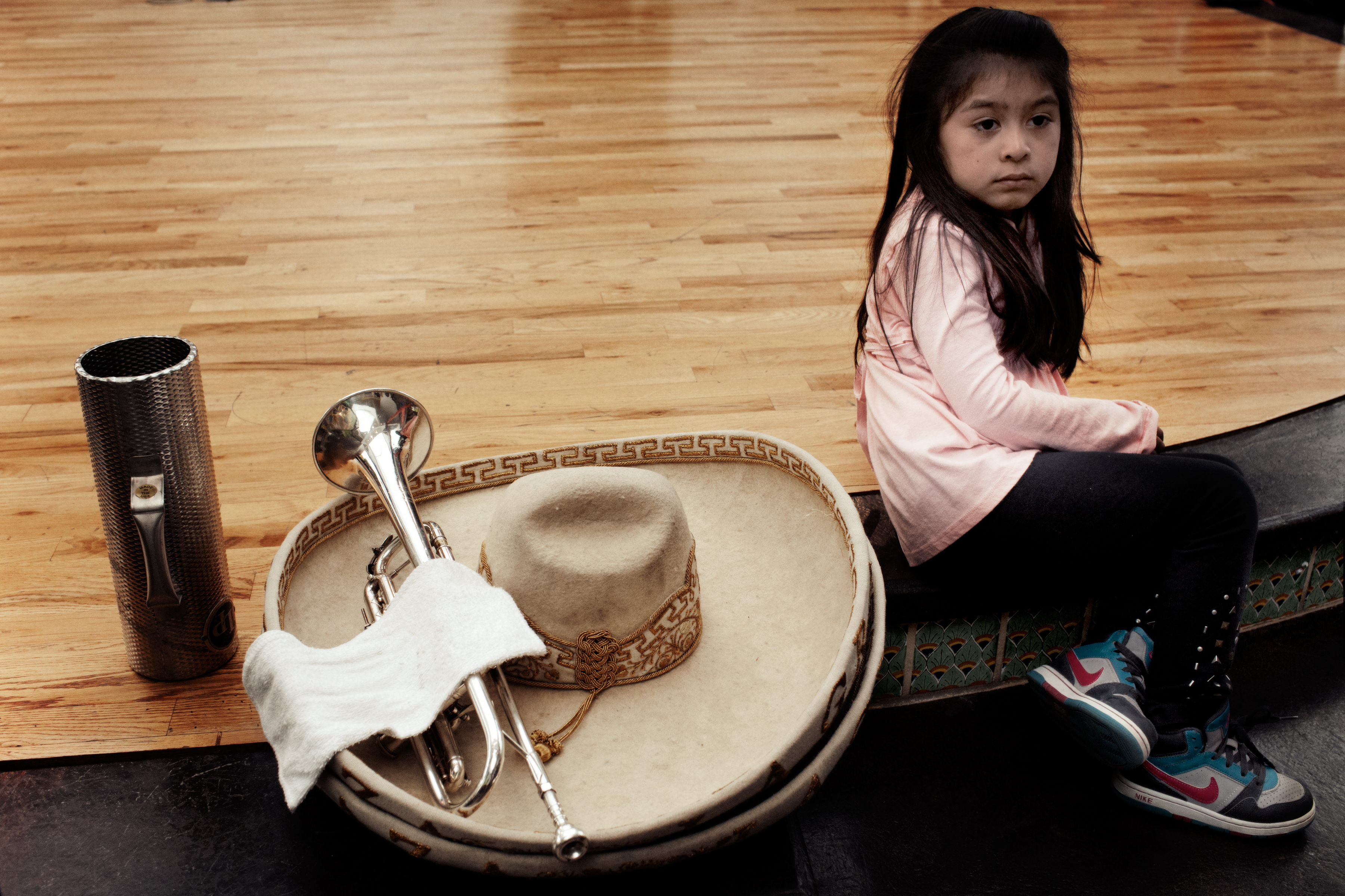 A girl sits on the edge of the stage beside a Mariachi's sombrero and trumpet before the weekend's entertainment begins.
