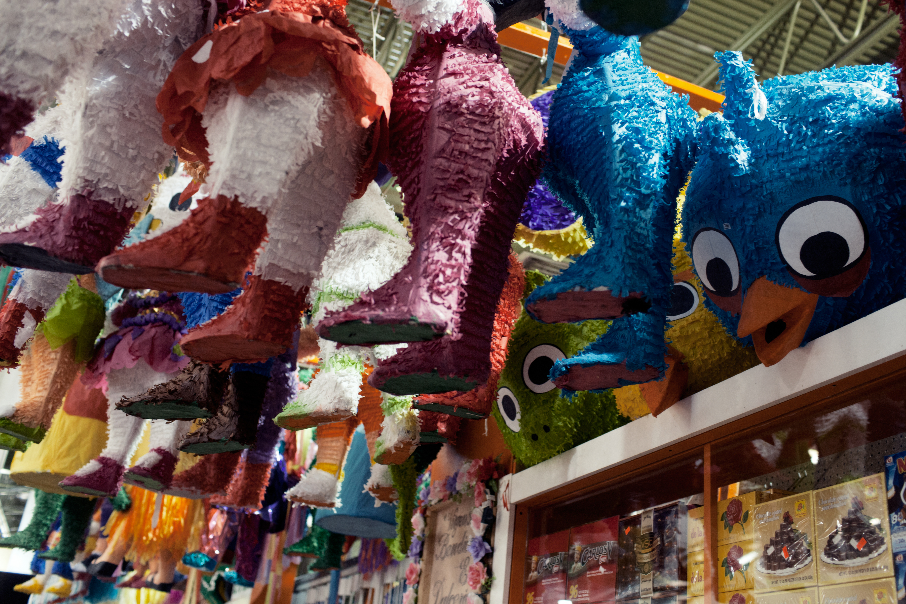 Piñatas hang from the ceiling in a store at the mall.