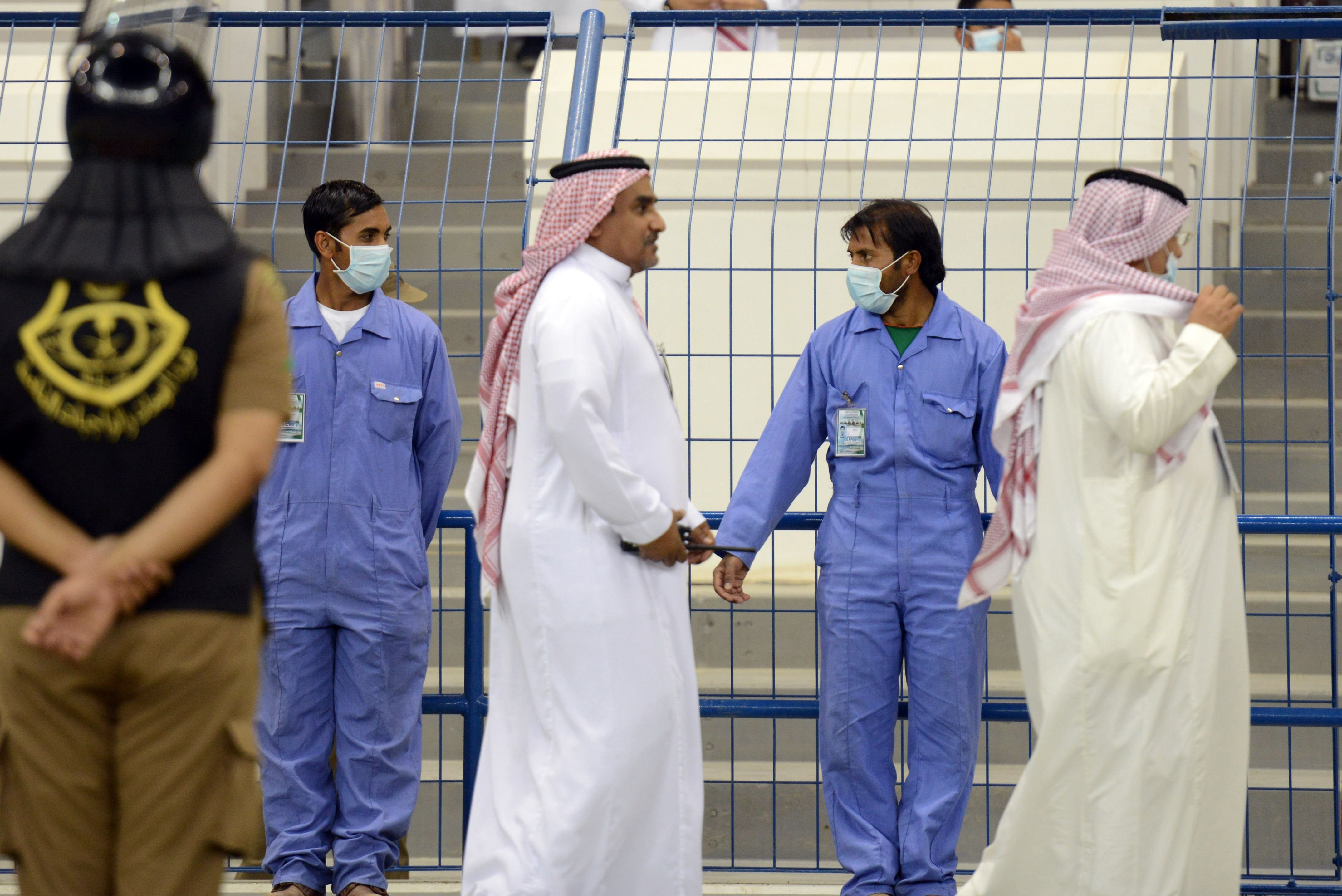 Asian workers wear mouth and nose masks while on duty during a football match at the King Fahad stadium, on April 22, 2014 in Riyadh. The health ministry reported more MERS cases in the city of Jeddah, prompting authorities to close the emergency department at the city's King Fahd Hospital.