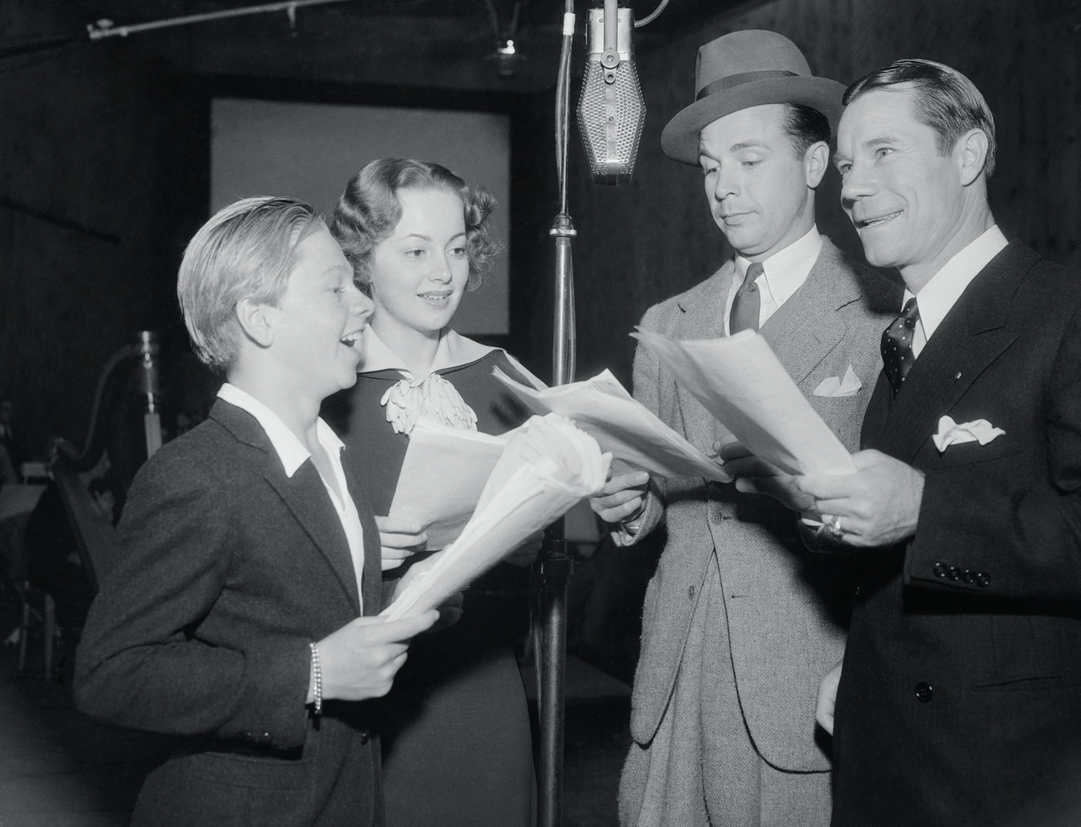 From left: Mickey Rooney, Olivia De Havilland, Dick Powell and Joe E. Brown under the microphone at the nation-wide broadcast from Los Angeles of A Midsummer Night's Dream on Oct. 10, 1935, in Los Angeles.