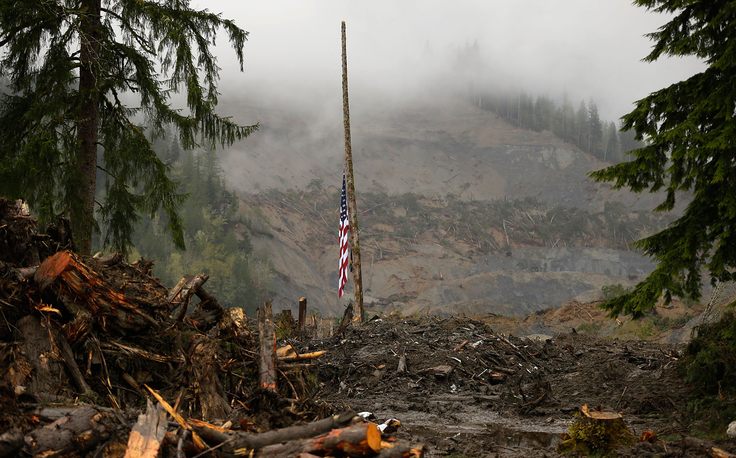 A flag rests at half staff on a cedar pole, Wednesday, April 16, 2014, with the face of the massive deadly mudslide that hit the community of Oso, Wash. on March 22, 2014 behind it.