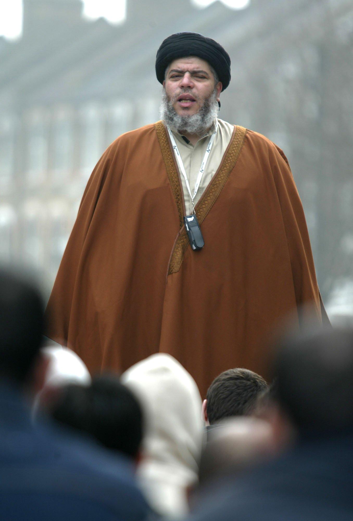 Muslim cleric Mustafa Kamel Mustafa prays in a street outside his Mosque in north London, on March 28, 2003.