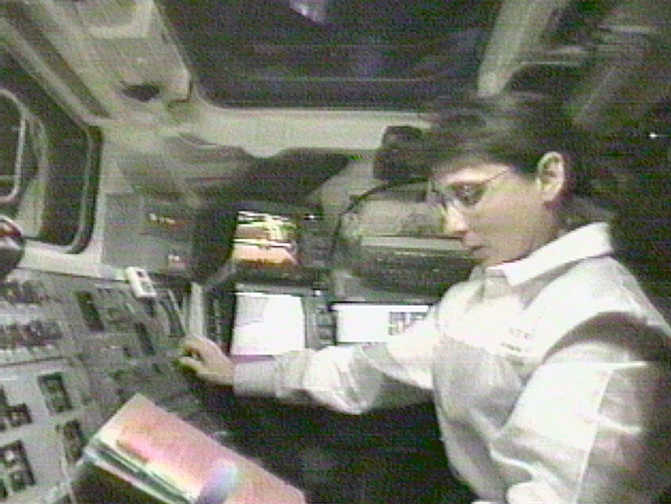 NASA Astronaut Nancy Currie reads a manual as she grapples an arriving space station module, in the cargo bay of the Endeavour, on Dec. 6, 1998.