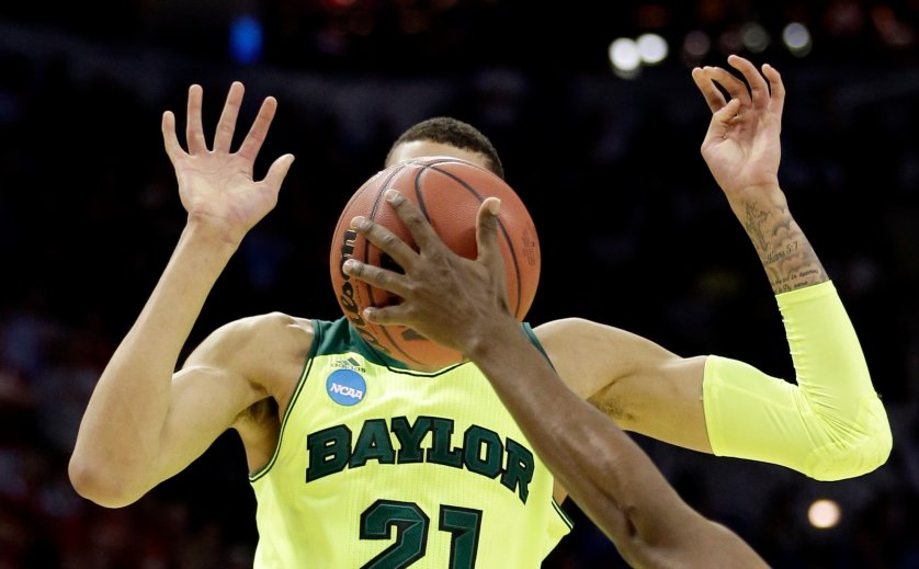 Baylor's Isaiah Austin has his face covered by the ball as Nebraska's Leslee Smith's arm reaches for the ball during the second half of a second-round game in the NCAA college basketball tournament, March 21, 2014, in San Antonio. Baylor won 74-60.