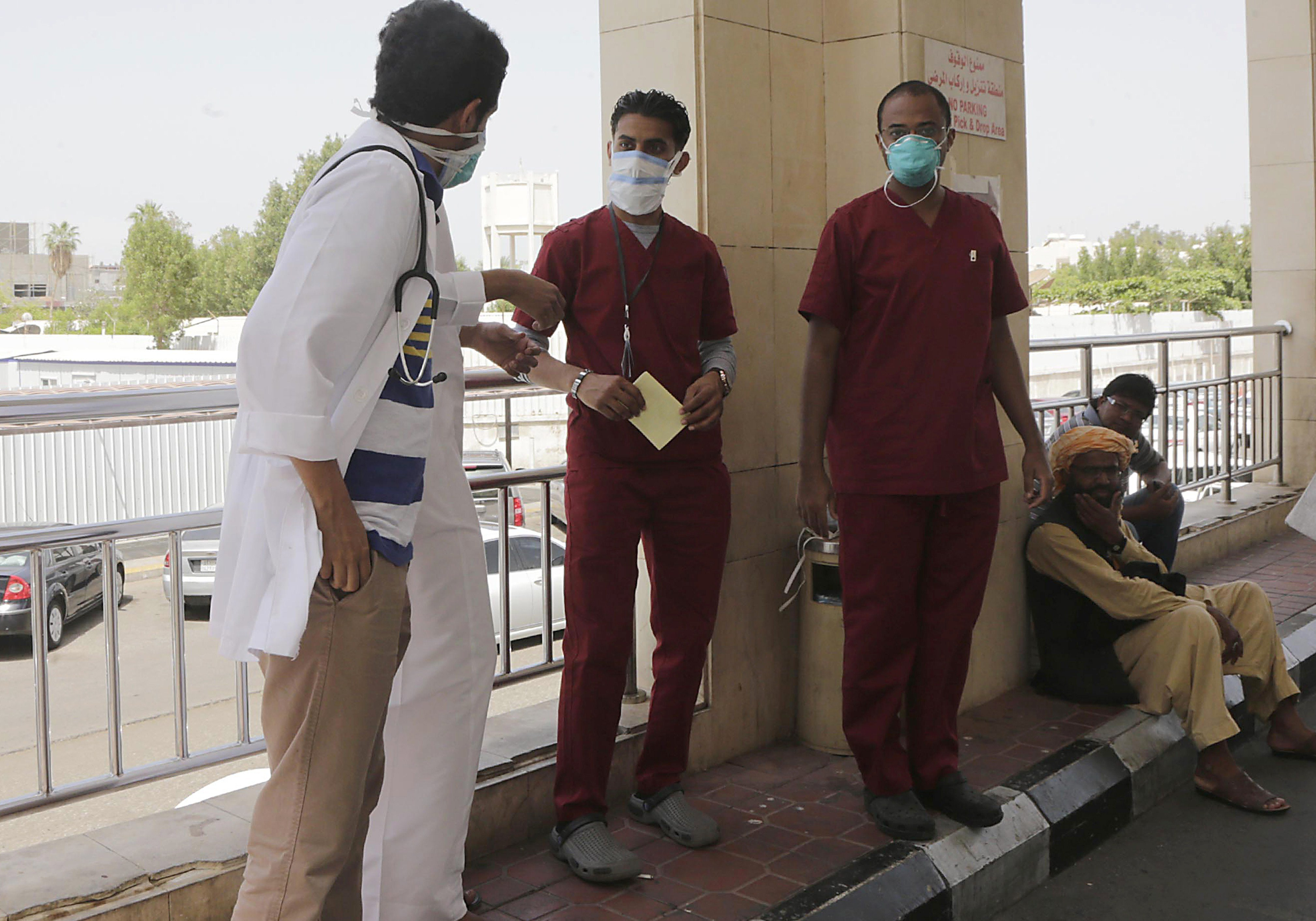 Saudi hospital employees wear mouth and nose masks as they stand outside the a local hospital's emergency department, on April 22, 2014 in the Red Sea coastal city of Jeddah. Egypt's Ministry of Health has confirmed that an Egyptian citizen who had recently returned from Saudi Arabia is infected with the virus.