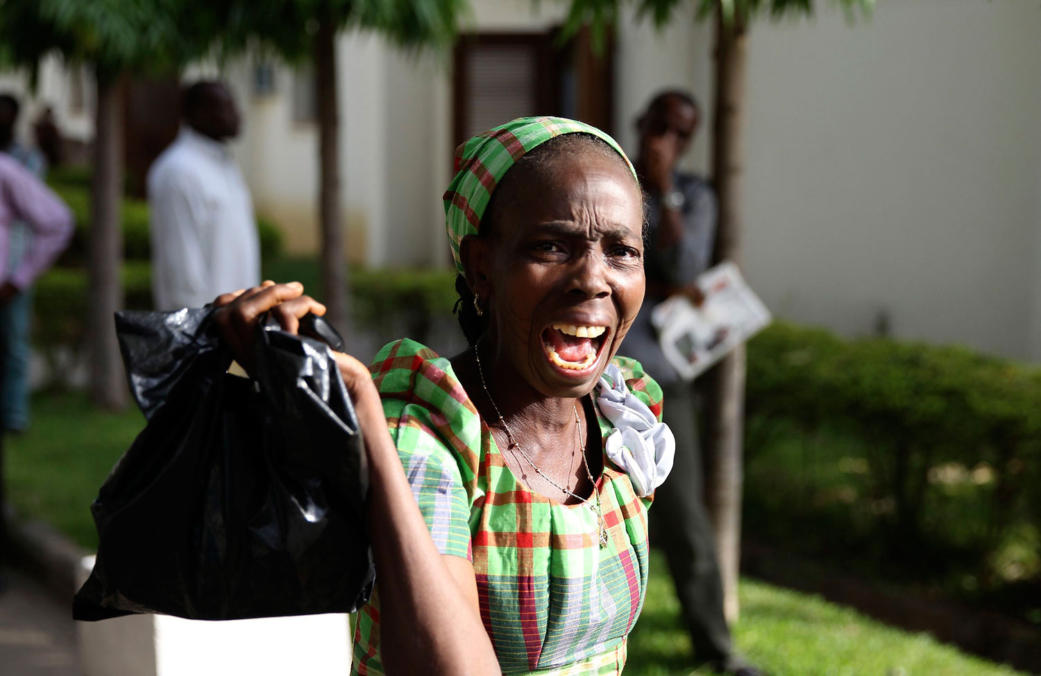 A bystander reacts as she sees victims of a bomb blast arriving at the Asokoro General Hospital in Abuja, April 14, 2014.
