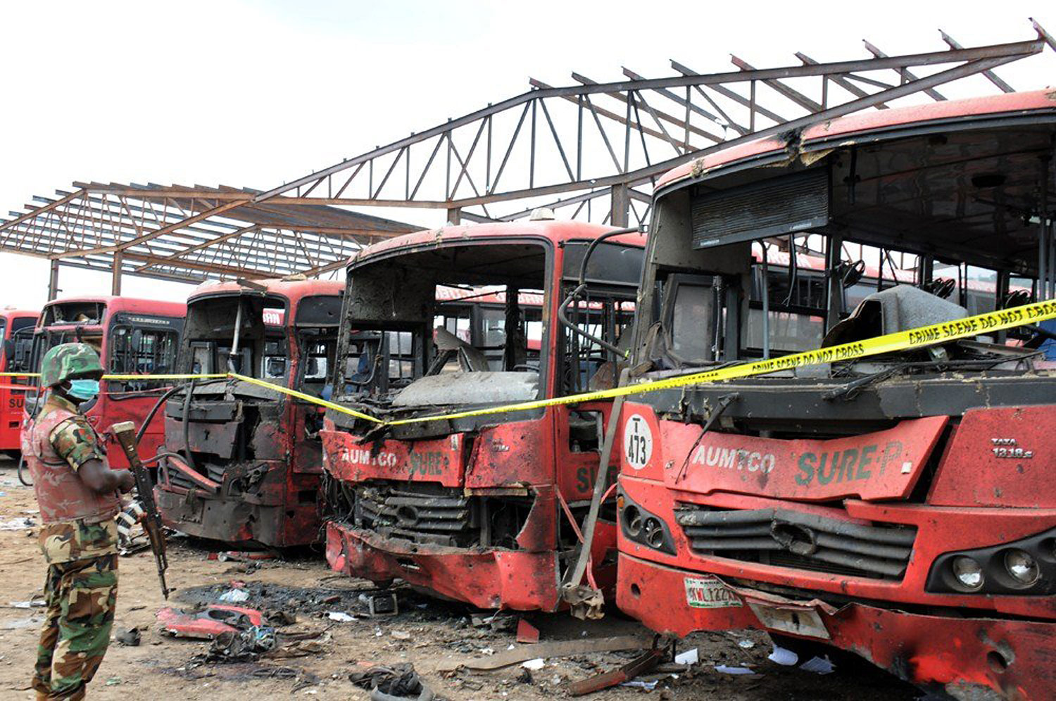 A soldier stands guard in front of burnt buses after an attack in Abuja, on April 14, 2014.