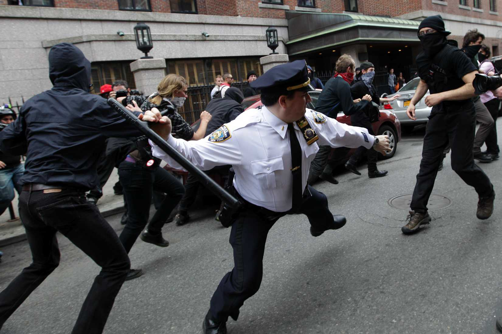 A police lieutenant swings his baton at Occupy Wall Street activists in New York City on May 1, 2012.