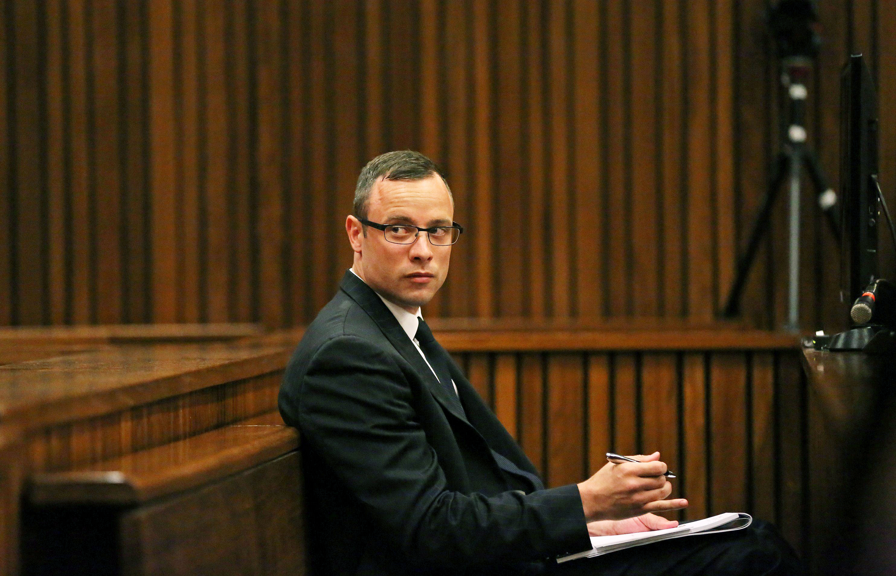Paralympic track star Oscar Pistorius sits in the dock during his trial for the murder of his girlfriend Reeva Steenkamp, at the North Gauteng High Court in Pretoria, on March 25, 2014.