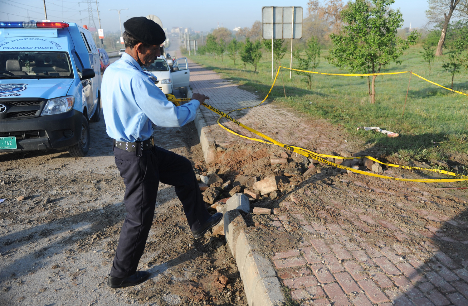 A Pakistani policeman rolls barricade tape at the site of a bomb explosion in Islamabad on April 3, 2014.