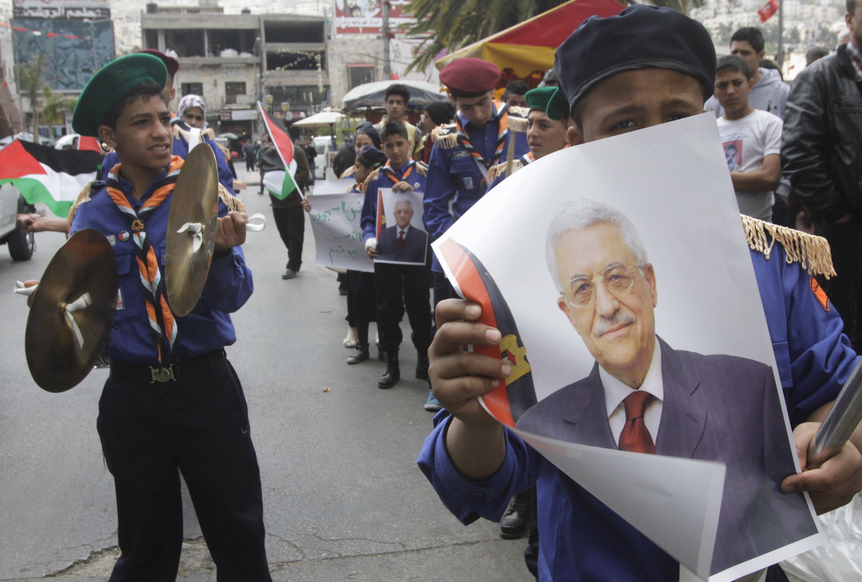 Scouts hold posters of Palestinian President Mahmoud Abbas during a Fatah rally in the West Bank city of Nablus on April 2, 2014