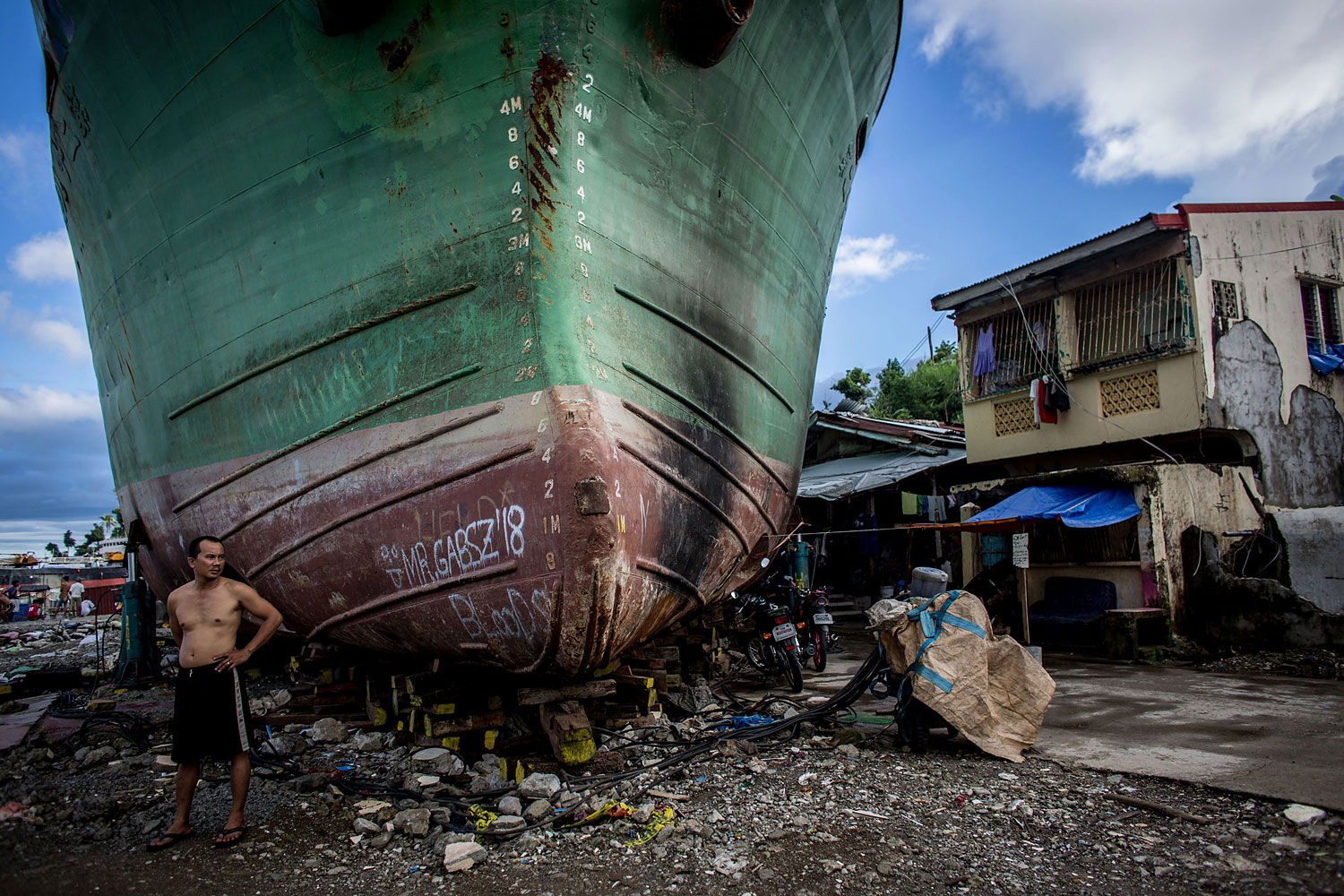 A man stands in front of a large ship grounded by Typhoon Haiyan on April 18, 2014 in Tacloban, Leyte, Philippines,