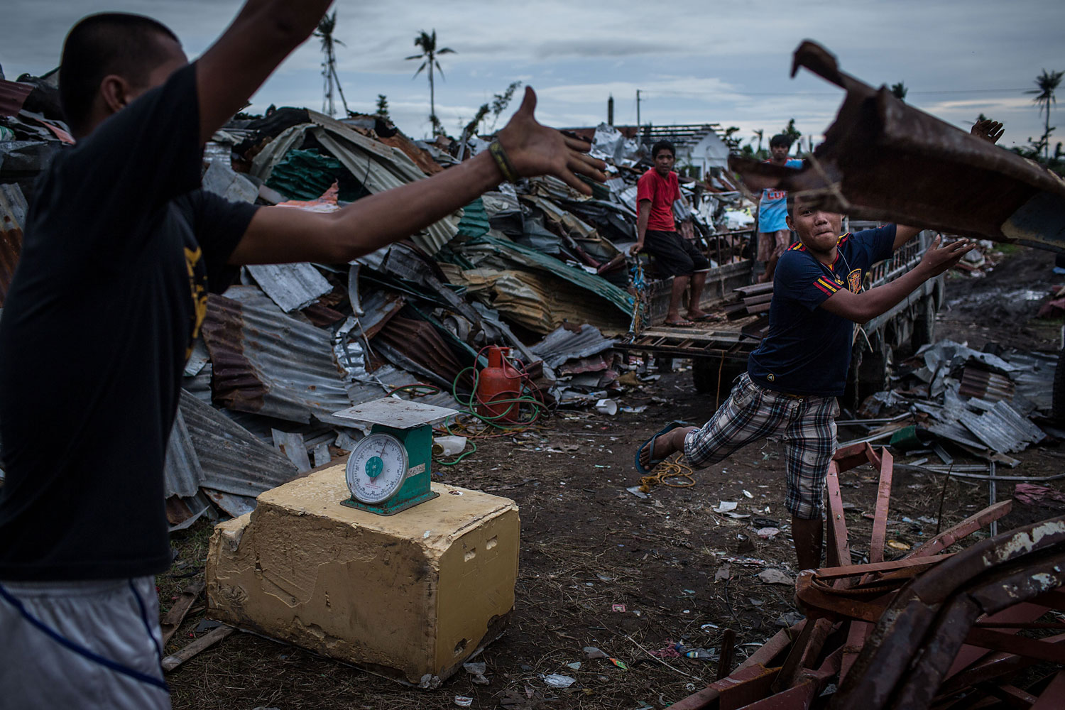 Workers at a junkyard throw scrap metal on a pile after weighing it on April 16, 2014 in Tacloban.