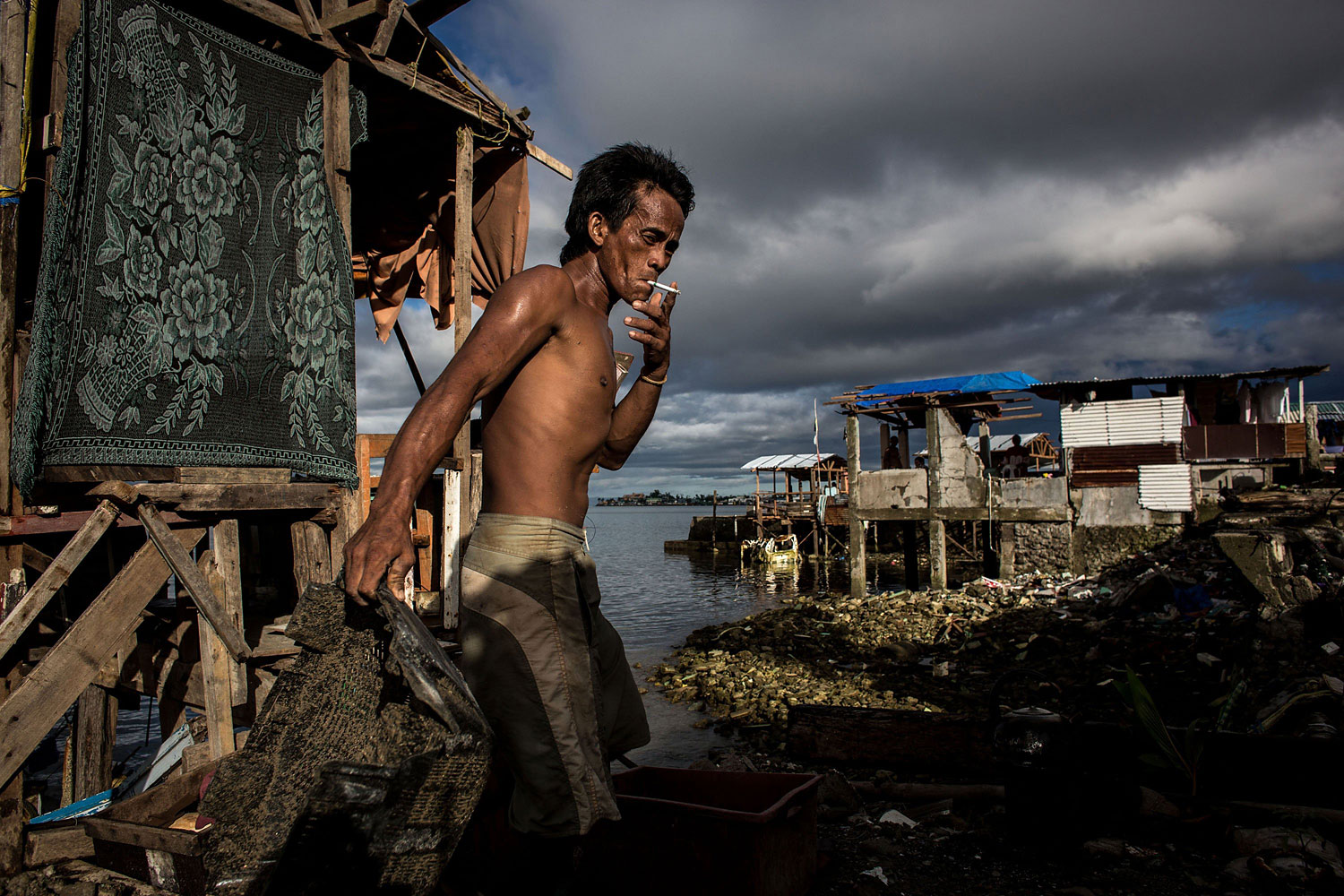 A man smokes as he removes rubble from his home on April 18, 2014 in Tacloban.