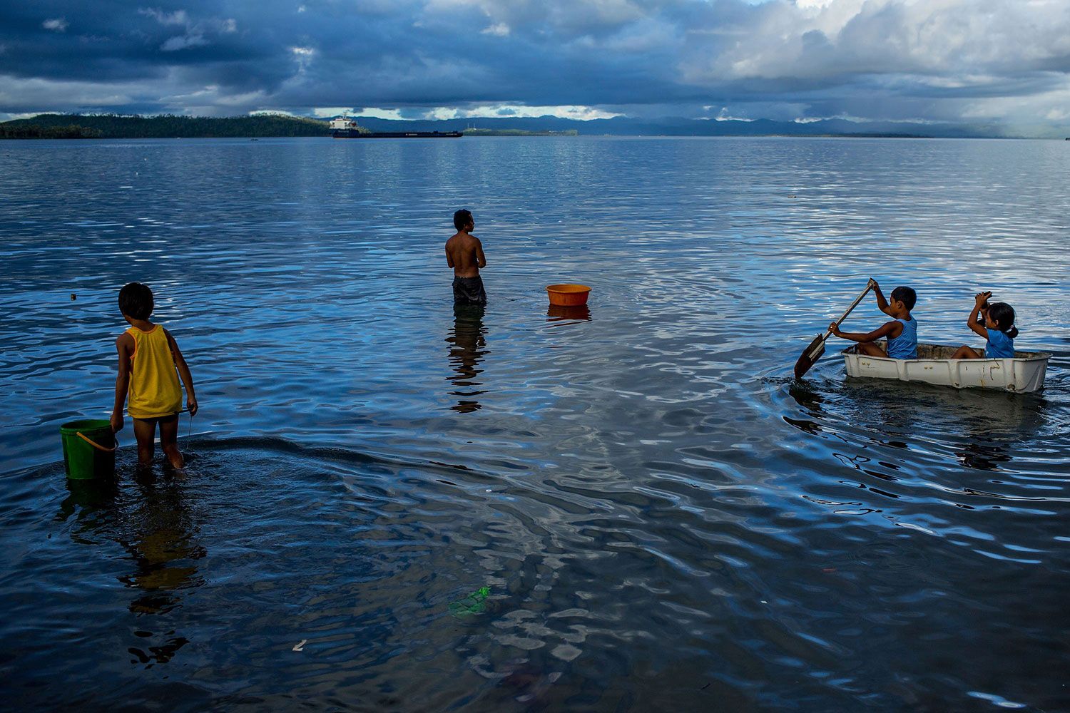 People enjoy the water off the coast of a destroyed town on April 18, 2014 in Tacloban.