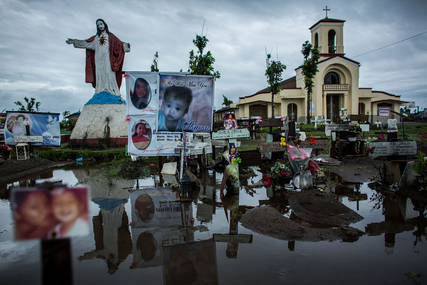 Crosses and personal items are seen at the makeshift mass grave site at San Joaquin Parish on April 16, 2014 in Tacloban.