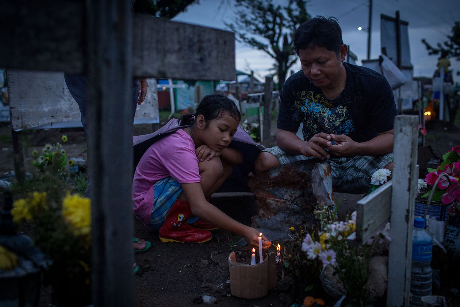 Jonna Lizette C. Modesto lights candles at the gravesite of her 5-year old brother John Reyneud C. Modesto watched on by her father Anastacio S. Modesto III at the makeshift mass grave site at San Joaquin Parish on April 16, 2014 in Tacloban.