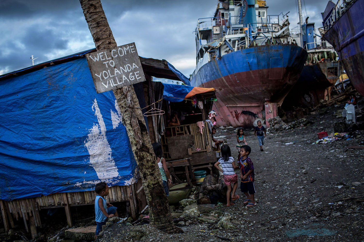 Children play around three large ships grounded by Typhoon Haiyan in the coastal area renamed by residents as 'Yolanda Village' on April 18, 2014 in Tacloban. Typhoon Haiyan is known as Yolanda in the Philippines.