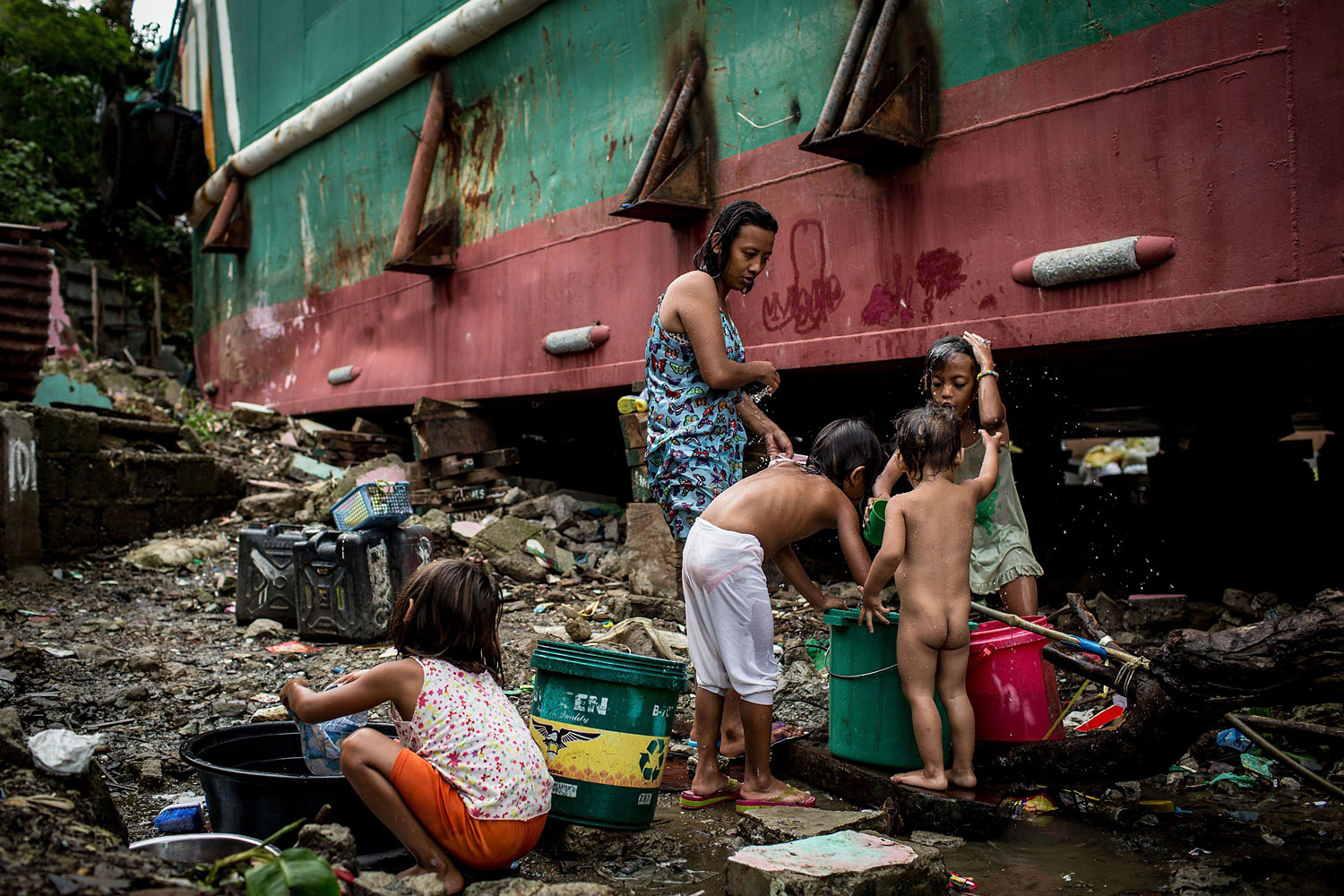 A family washes and cleans clothes next to the hull of a large ship grounded by Typhoon Haiyan on April 18, 2014 in Tacloban.