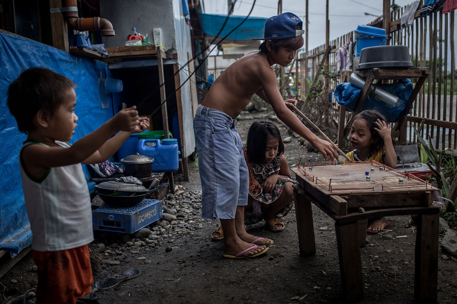 Kids watch on as a boy plays pool with marbles on a makeshift pool table in a temporary bunk house complex on April 16, 2014 in Tacloban.