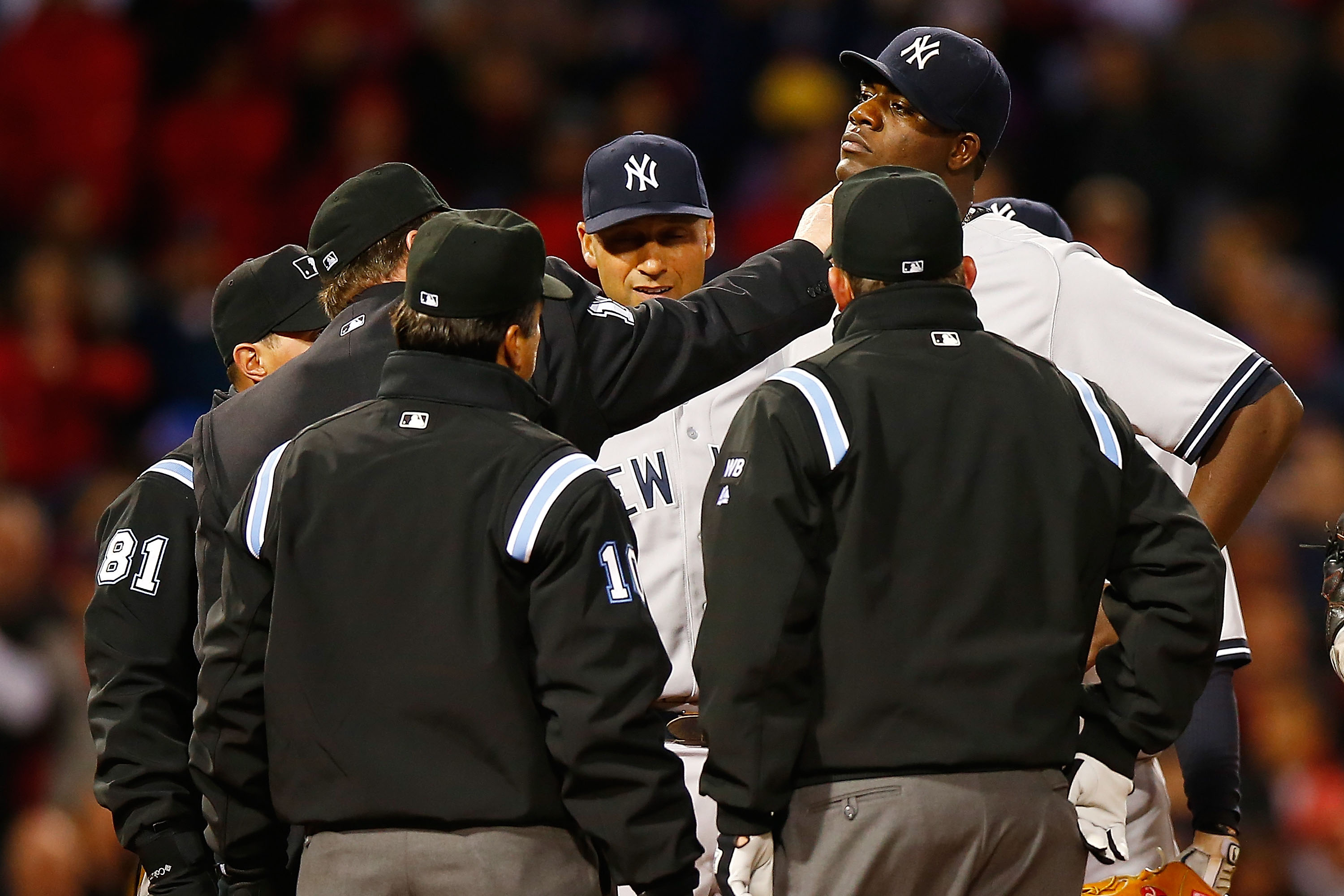 Home plate umpire Gerry Davis checks out a substance on the neck of Michael Pineda as New York Yankees shortstop Derek Jeter looks on.