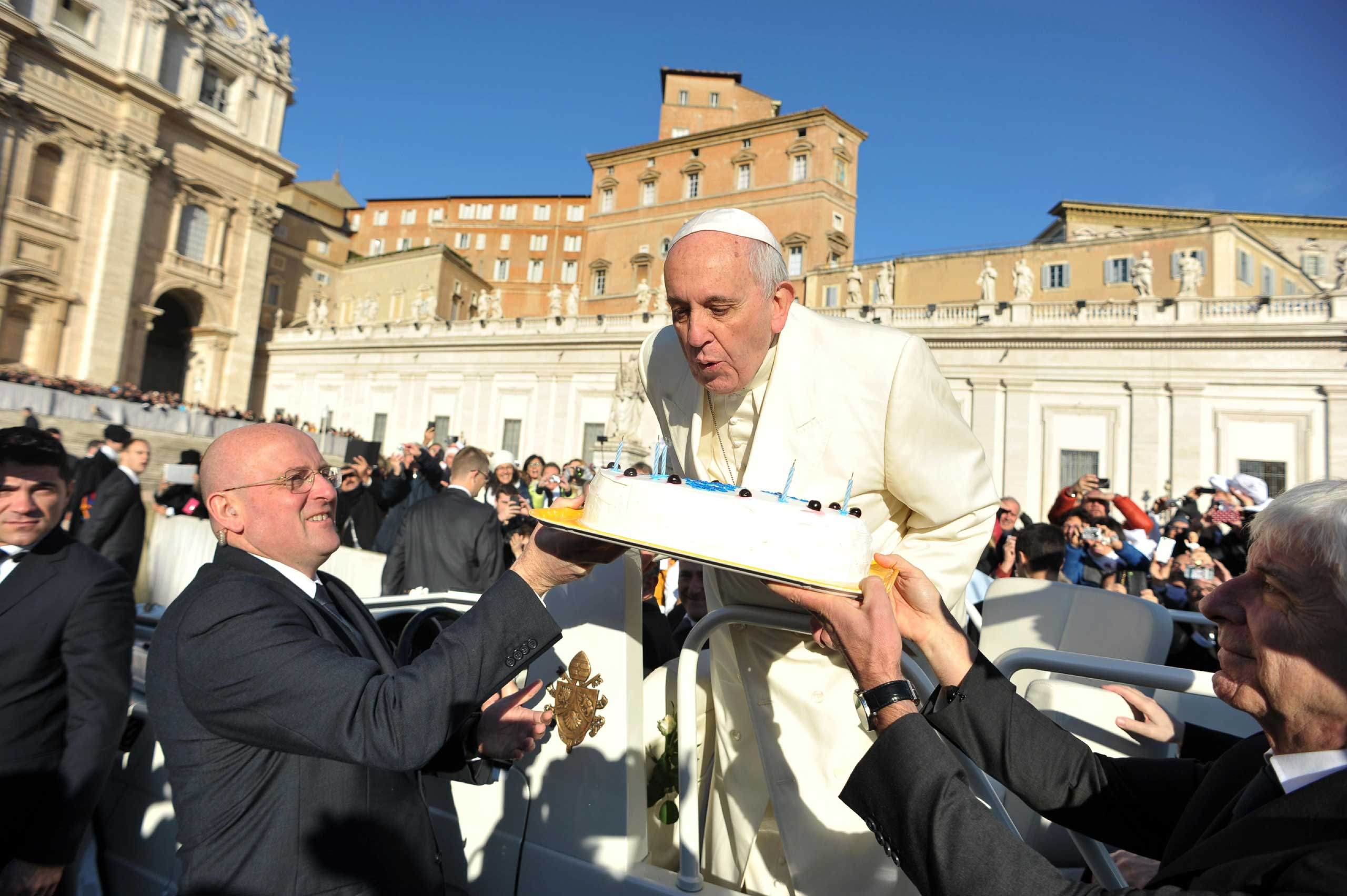 Pope Francis blows out the candles of a birthday cake to celebrate his 78th birthday during a general audience at the Vatican on Dec. 17, 2014.