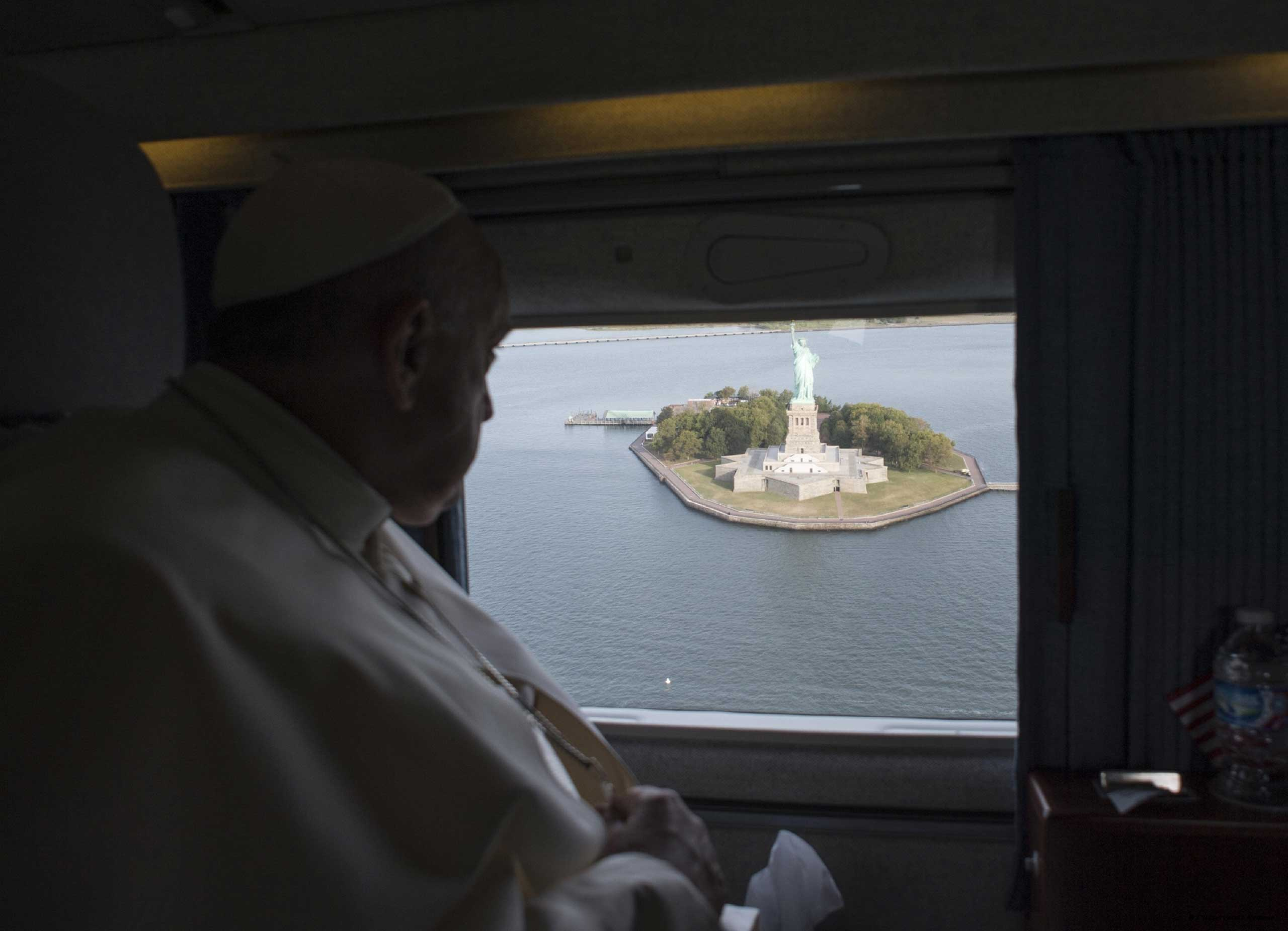 Pope Francis looks at the Statue of Liberty from the window of a helicopter on his way to the John F. Kennedy International Airport, in New York City, on Sept. 26, 2015.