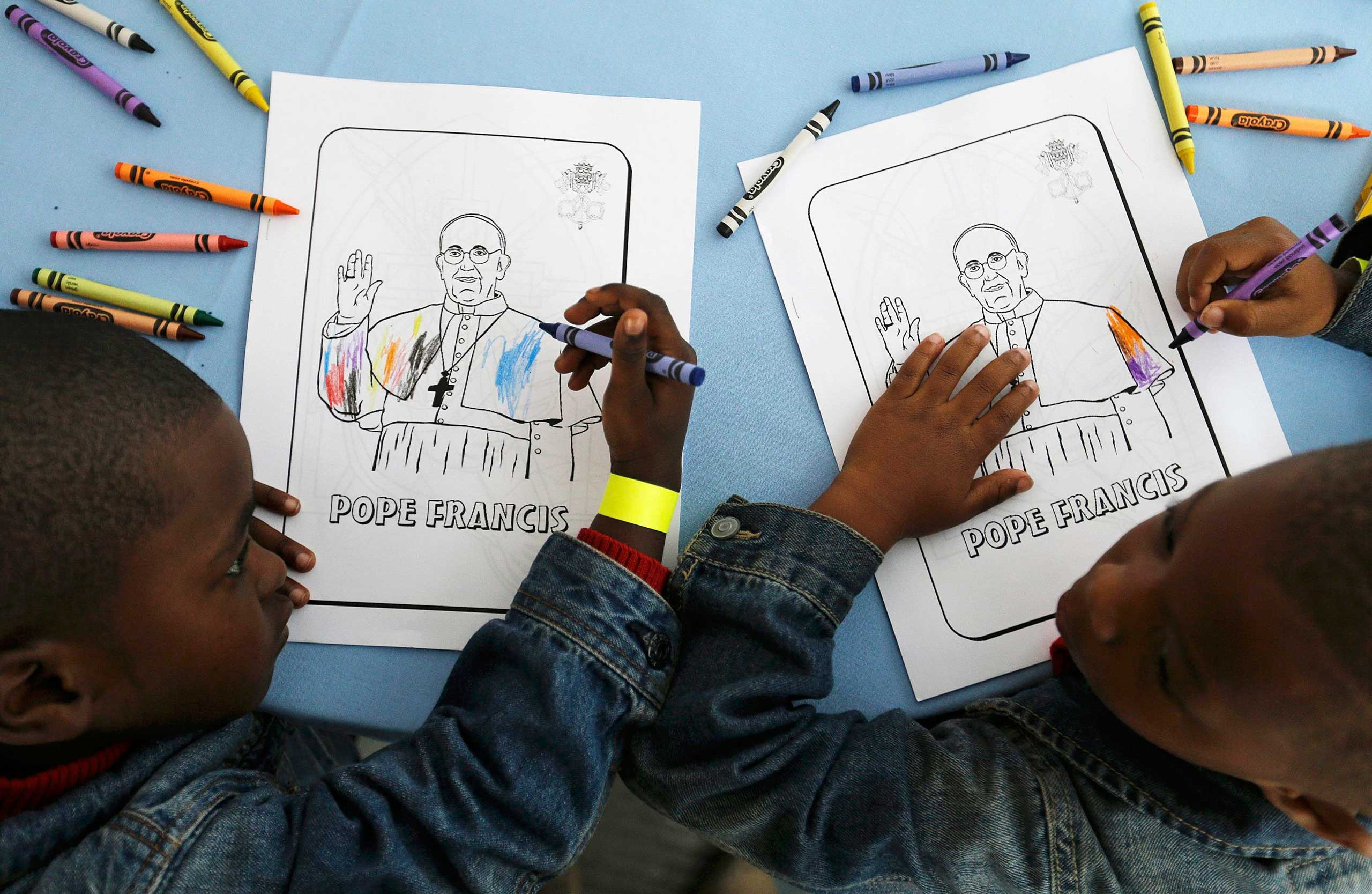 Kaydn Dorsey, 4, and Lionel Perkins, 4, draw on a coloring sheet bearing the image of Pope Francis as they wait for him to arrive on a visit to Catholic Charities of the Archdiocese of Washington in Washington, on Sept. 24, 2015.
