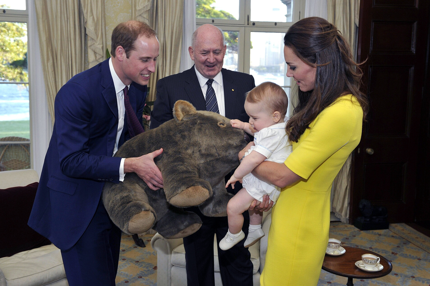 Prince George of Cambridge, with his parents Prince William, Duke of Cambridge and Catherine, Duchess of Cambridge, receives a gift from the Governor-General, Sir Peter Cosgrove, at Admiralty House, on April 16, 2014 in Sydney. The Duke and Duchess of Cambridge are on a three-week tour of Australia and New Zealand, the first official trip overseas with their son, Prince George of Cambridge.