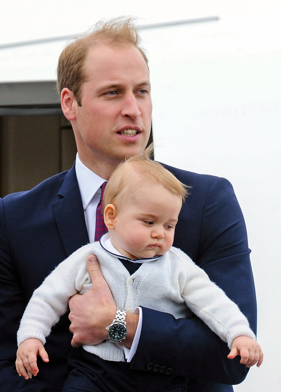 Prince William, Duke of Cambridge, holds Prince George as they board a Royal Australian Airforce Jet heading to Sydney at an airport in Wellington, New Zealand, April 16, 2014. The Duke and Duchess of Cambridge will be in Australia until April 25, 2014.