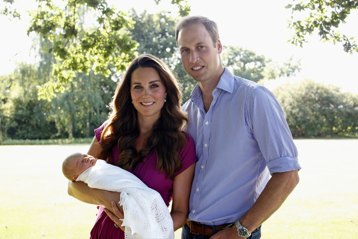 Catherine, Duchess of Cambridge and Prince William, Duke of Cambridge pose for a photograph with their son, Prince George Alexander Louis of Cambridge in the garden of the Middleton family home in August, 2013, in Bucklebury, Berkshire.