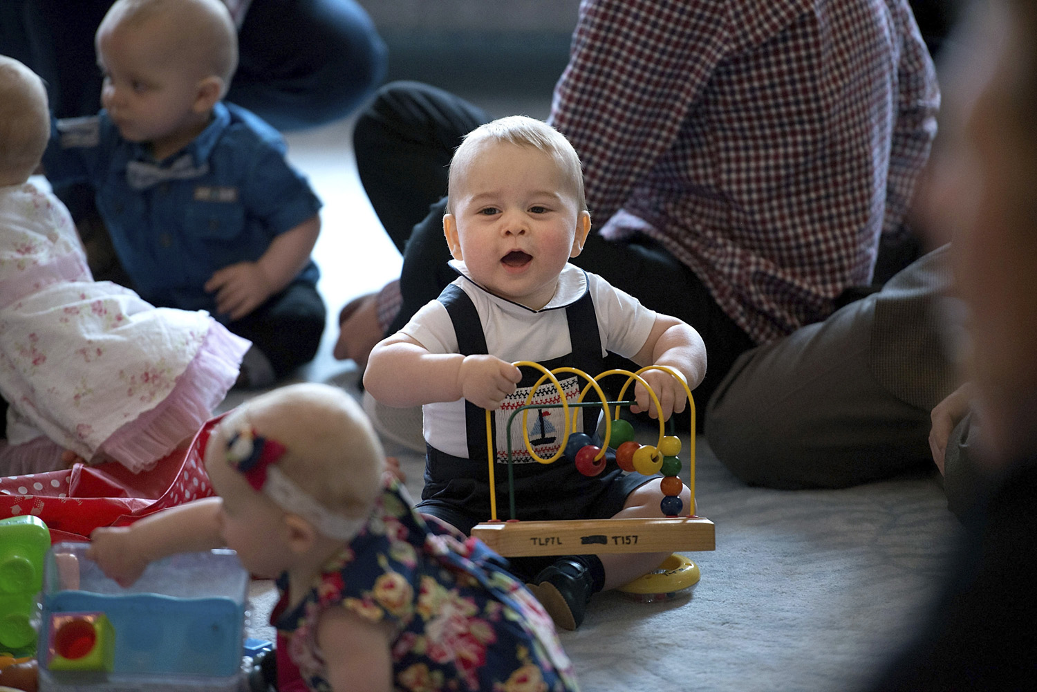 Britain's Prince George, center, plays during a visit to Plunket, a nurse and parents group at Government House in Wellington, New Zealand April 9, 2014.