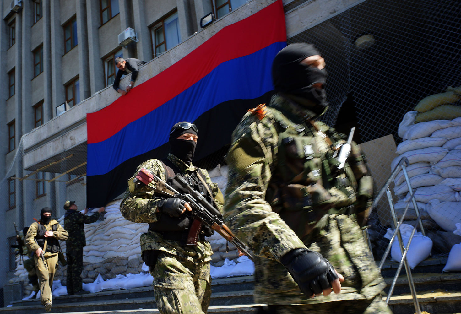 A pro-Russia activist hangs a flag of the so-called  People's Republic of Donetsk  on the regional administration building seized by separatists as armed men in military fatigues guard the premises in the eastern Ukrainian city of Slavyansk on April 21, 2014.