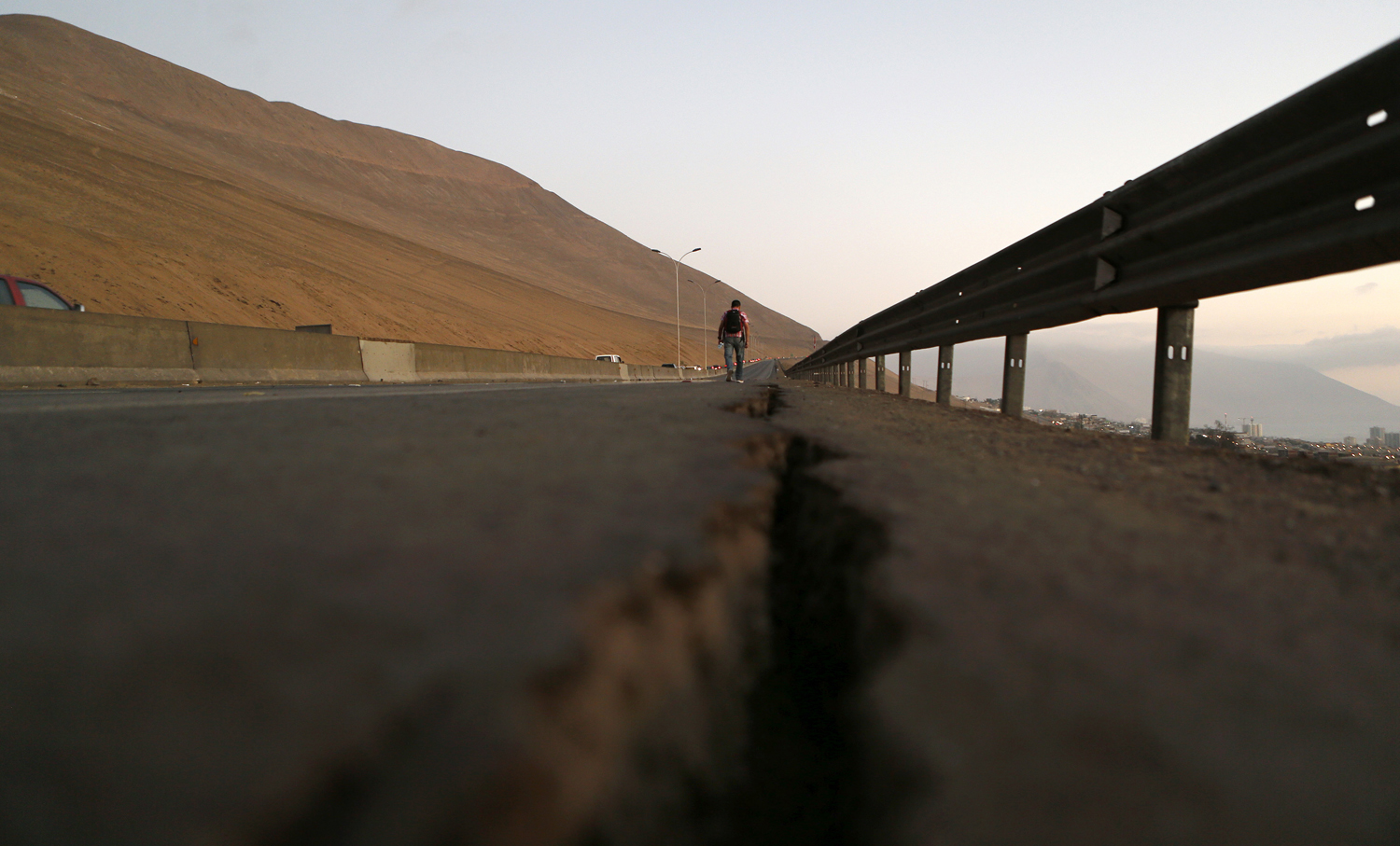 A resident walks along a damaged road to Alto Hospicio commune after an earthquake and tsunami hit the northern port of Iquique April 2, 2014.