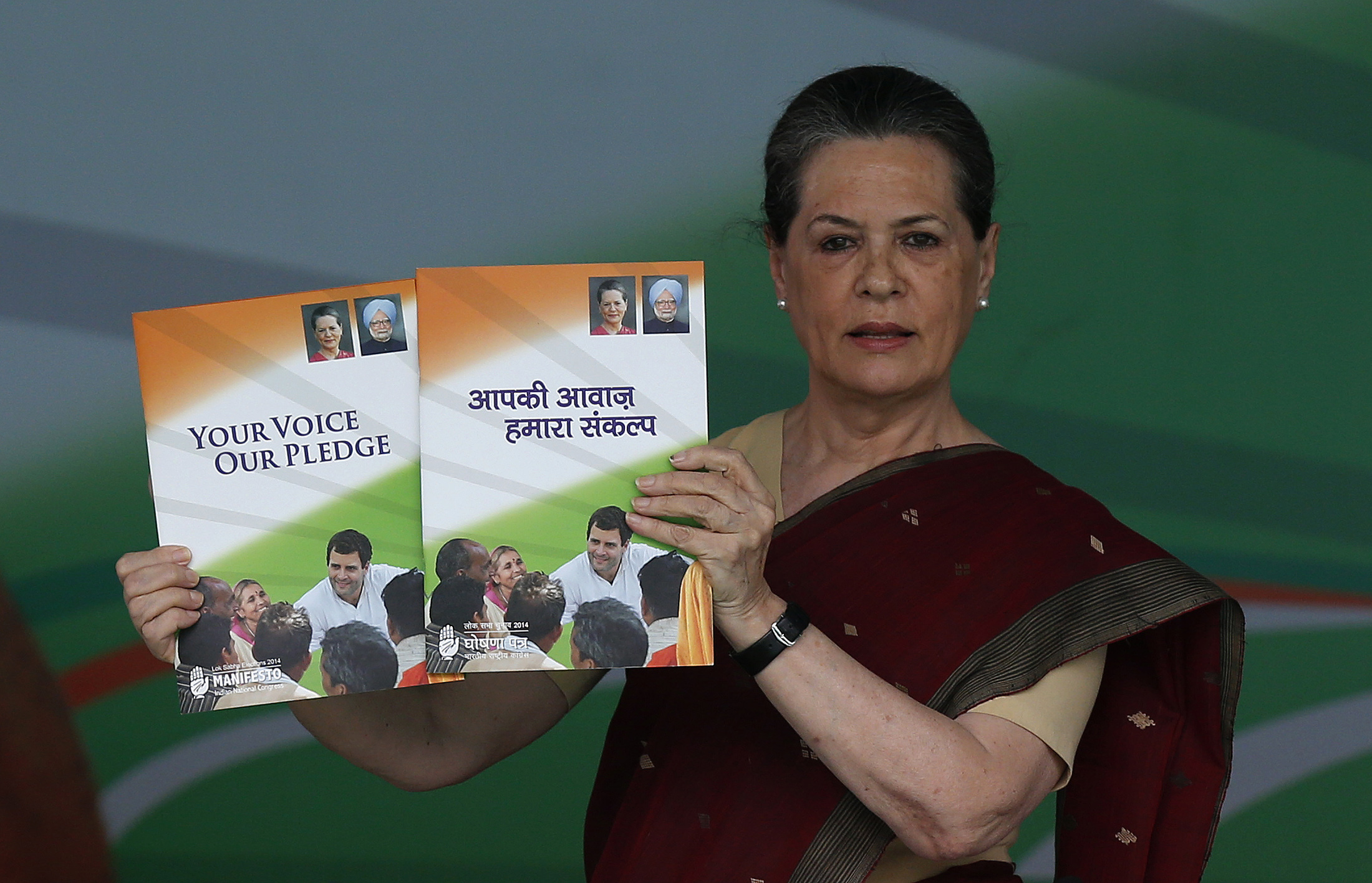 Sonia Gandhi, leader of the governing Congress Party, holds her party's manifesto for the 2014 general elections. She said Congress was fighting for the  heart and soul  of India