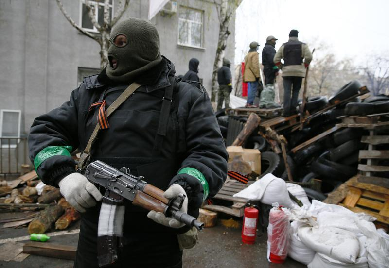 A masked separatist stands guard outside a government building in Slavyansk.
