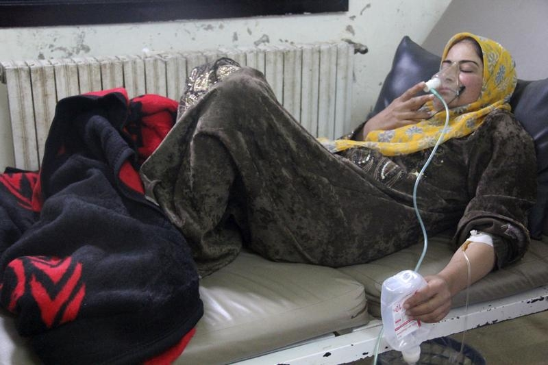 A woman affected by what activists say was a gas attack breathes through an oxygen mask inside a field hospital in Kfar Zeita village in syria on April 12, 2014.