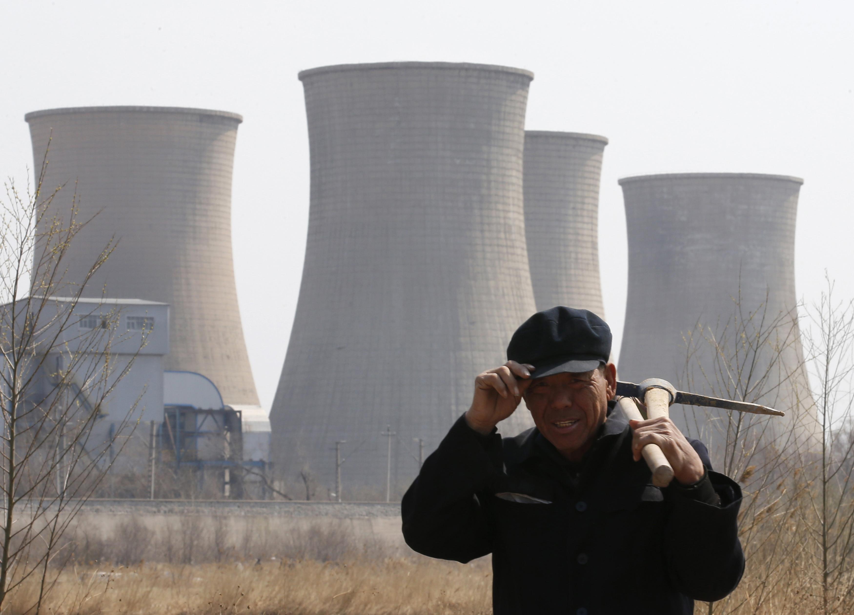 A worker walks past a steel factory in Beijing on April 1, 2013