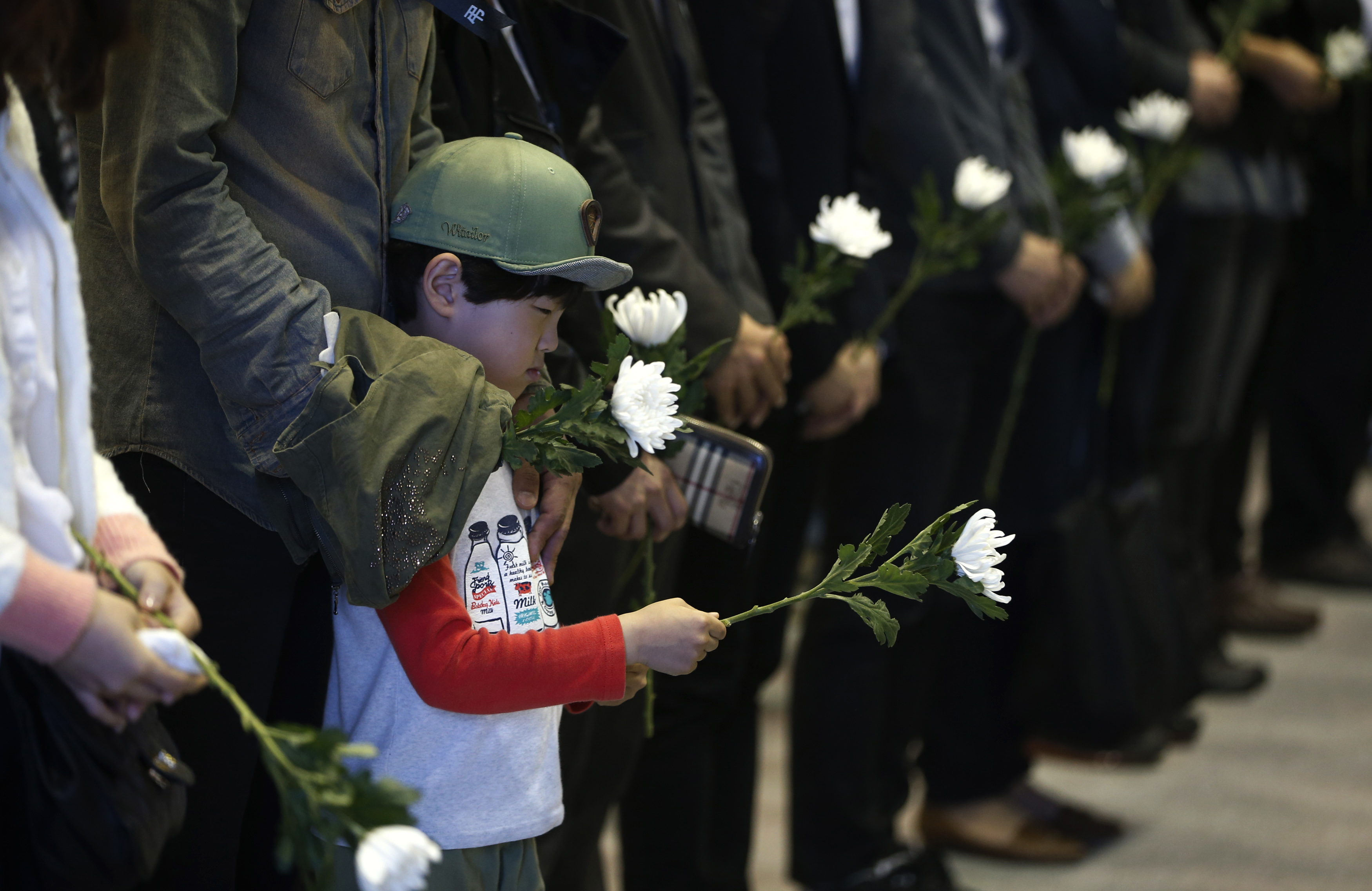 A boy holding a white chrysanthemum pays tribute at a temporary group memorial altar for victims of capsized passenger ship Sewol in Ansan, April 24, 2014.